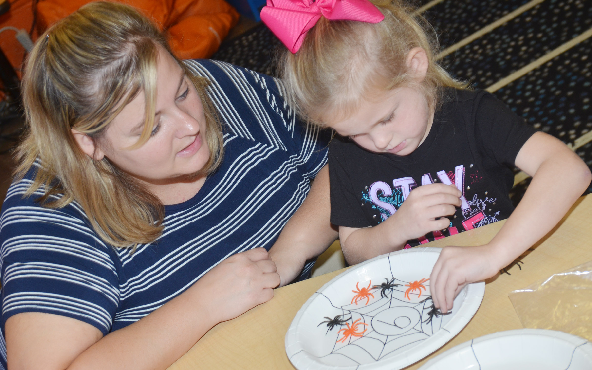 CES kindergarten teacher Kimberly Clark helps Riley Bright count with plastic spiders.