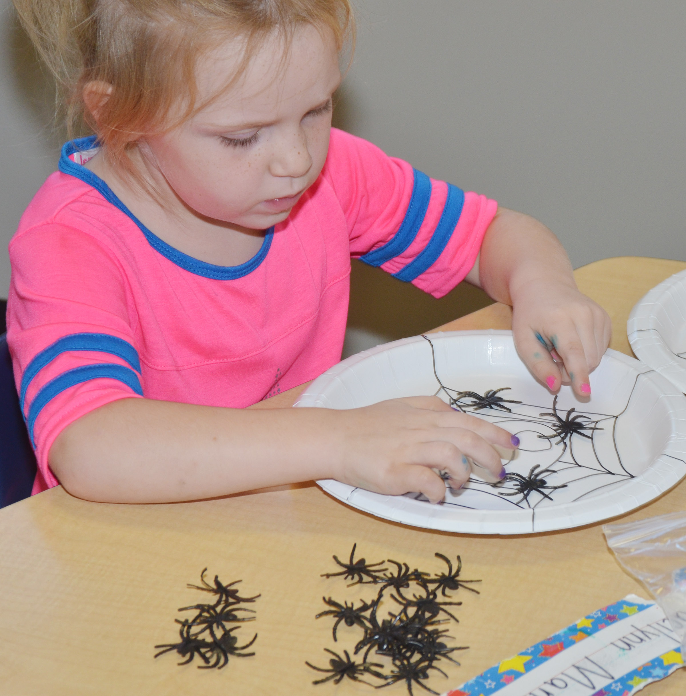 CES kindergartener Macilynn Mann counts with plastic spiders.