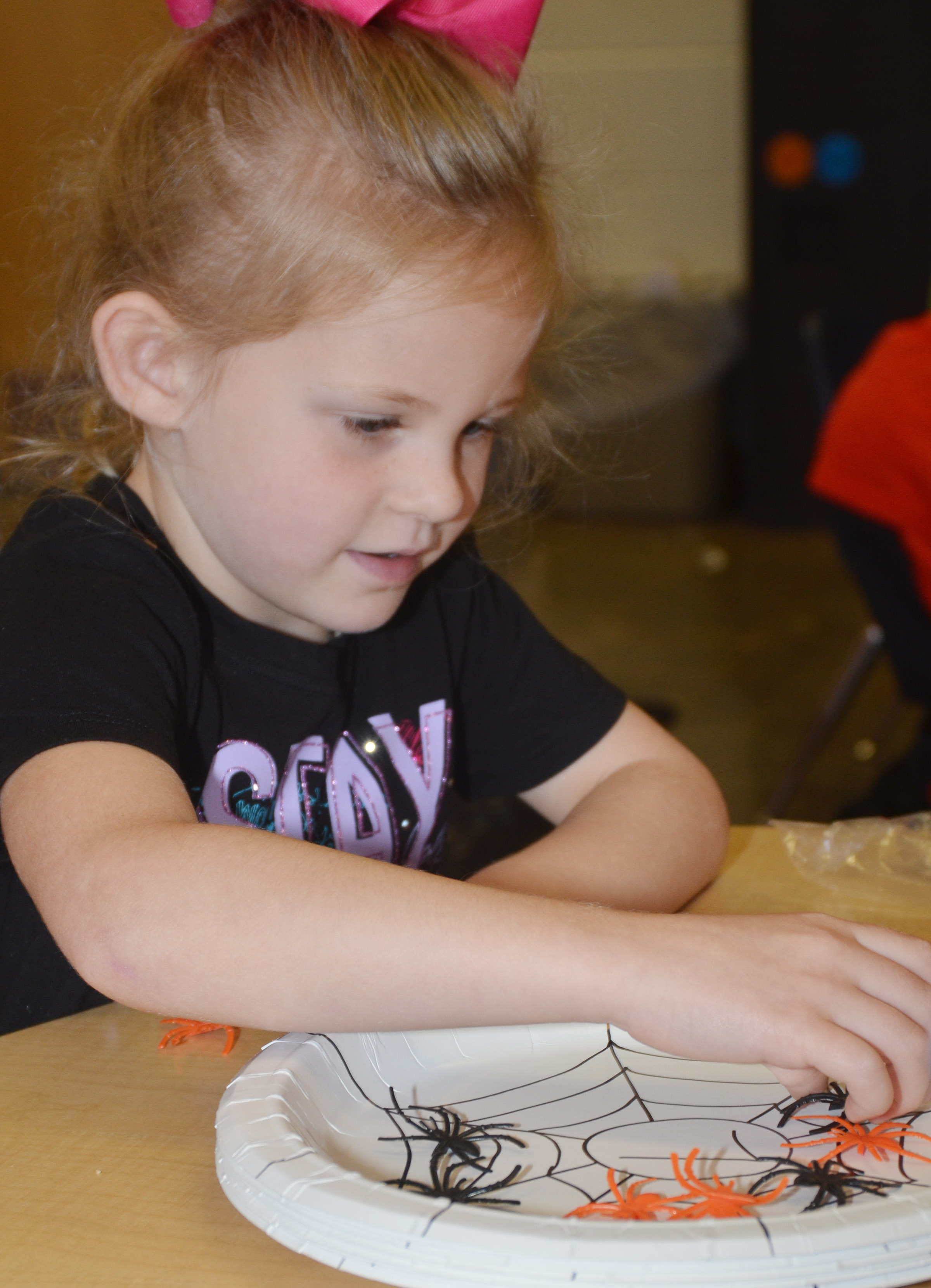 CES kindergartener Riley Bright counts with plastic spiders.