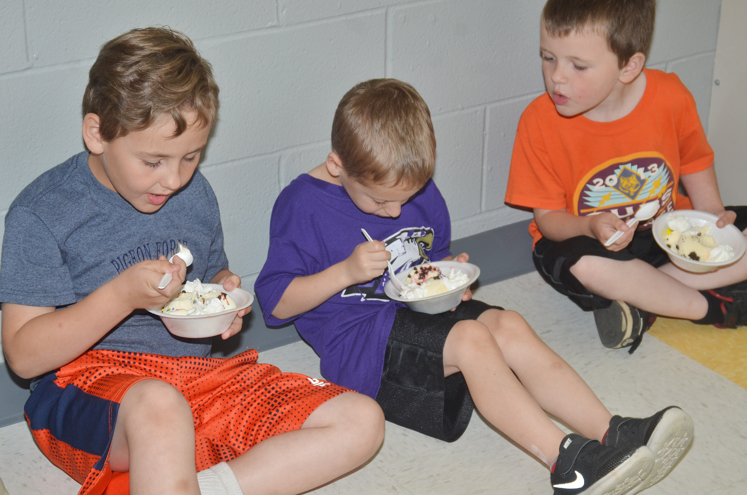 From left, CES kindergarteners Braxton Rhodes and Gavin Paris enjoy their ice cream sundaes as Mason Dowell sees what toppings they have.