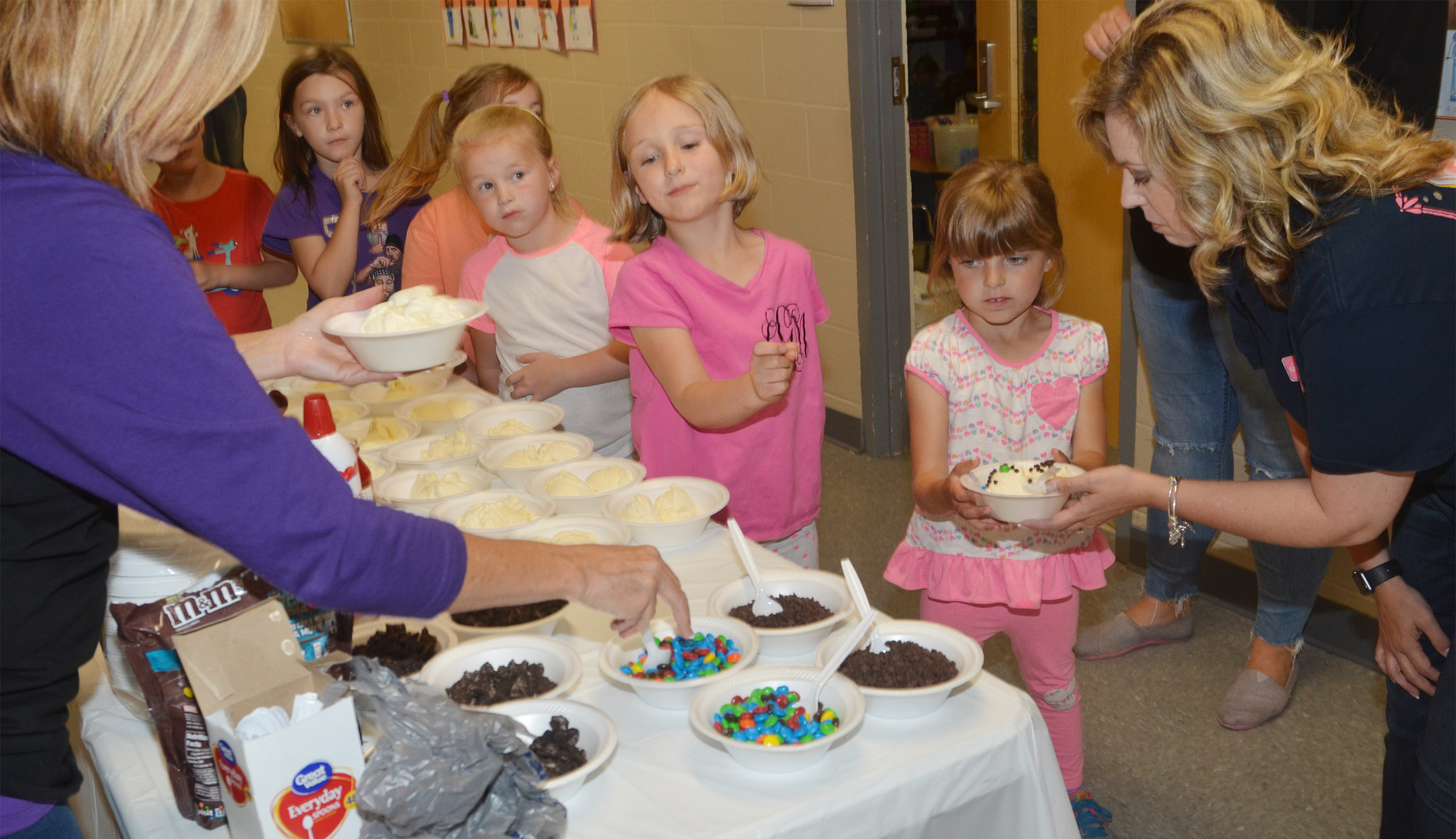CES kindergartener Madison Wilhoite is served her ice cream sundae.