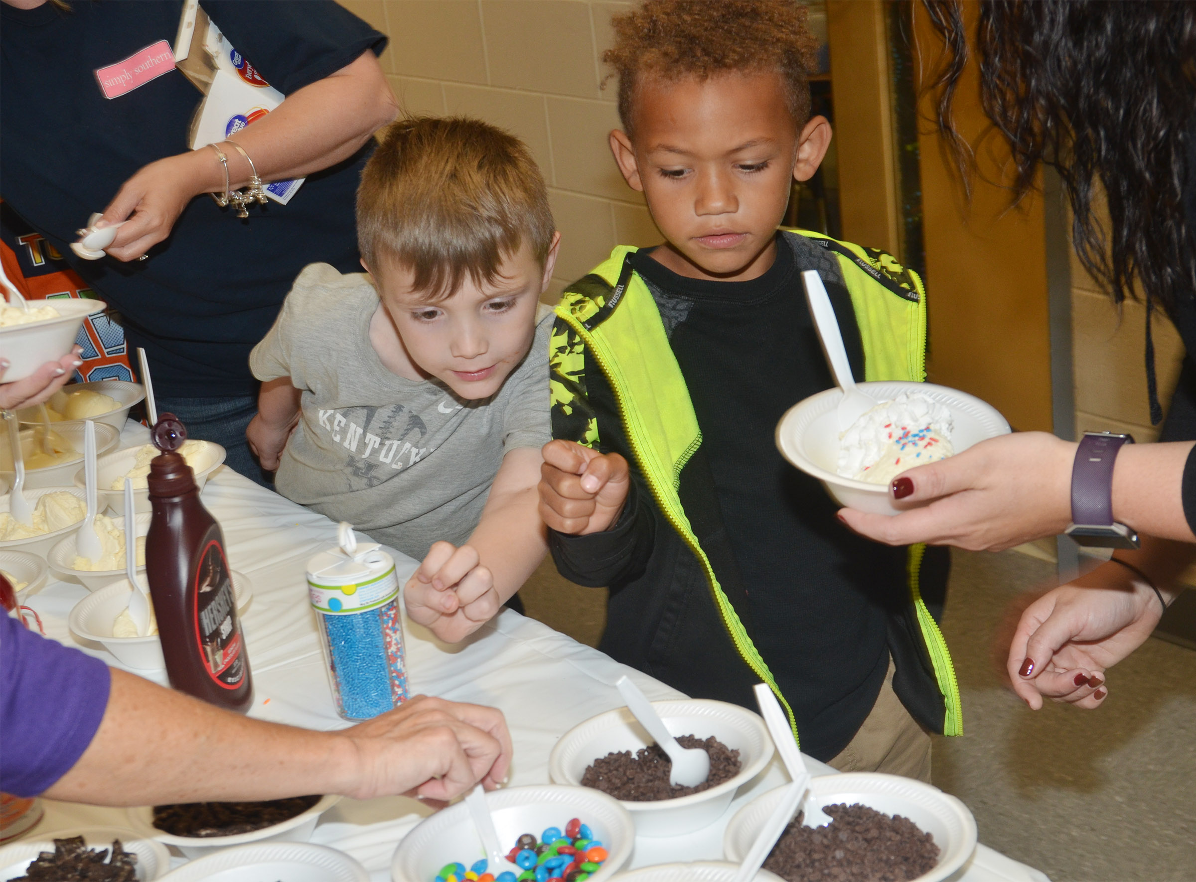 CES kindergarteners John Lane, at left, and Treshaun Robinson are served their ice cream sundaes.