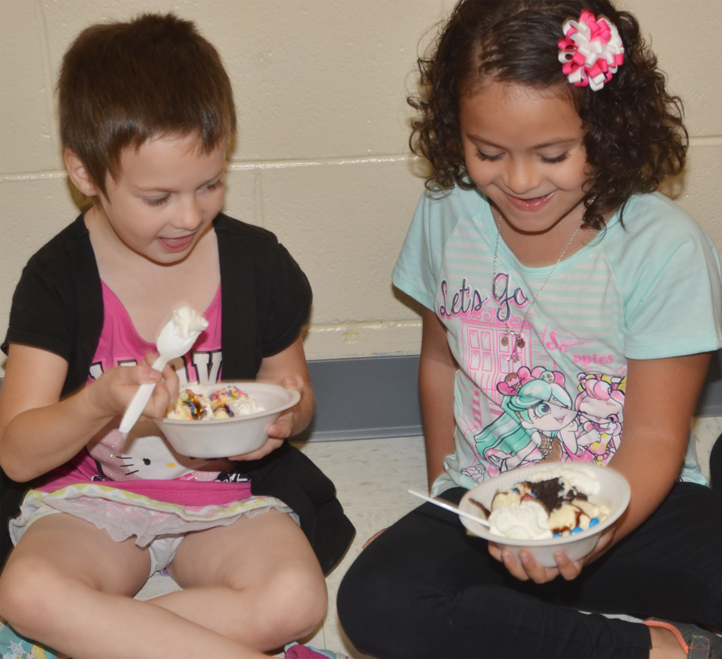 CES kindergarteners Madison Haywood, at left, and Isabella Anderson talk as they enjoy their ice cream sundaes.