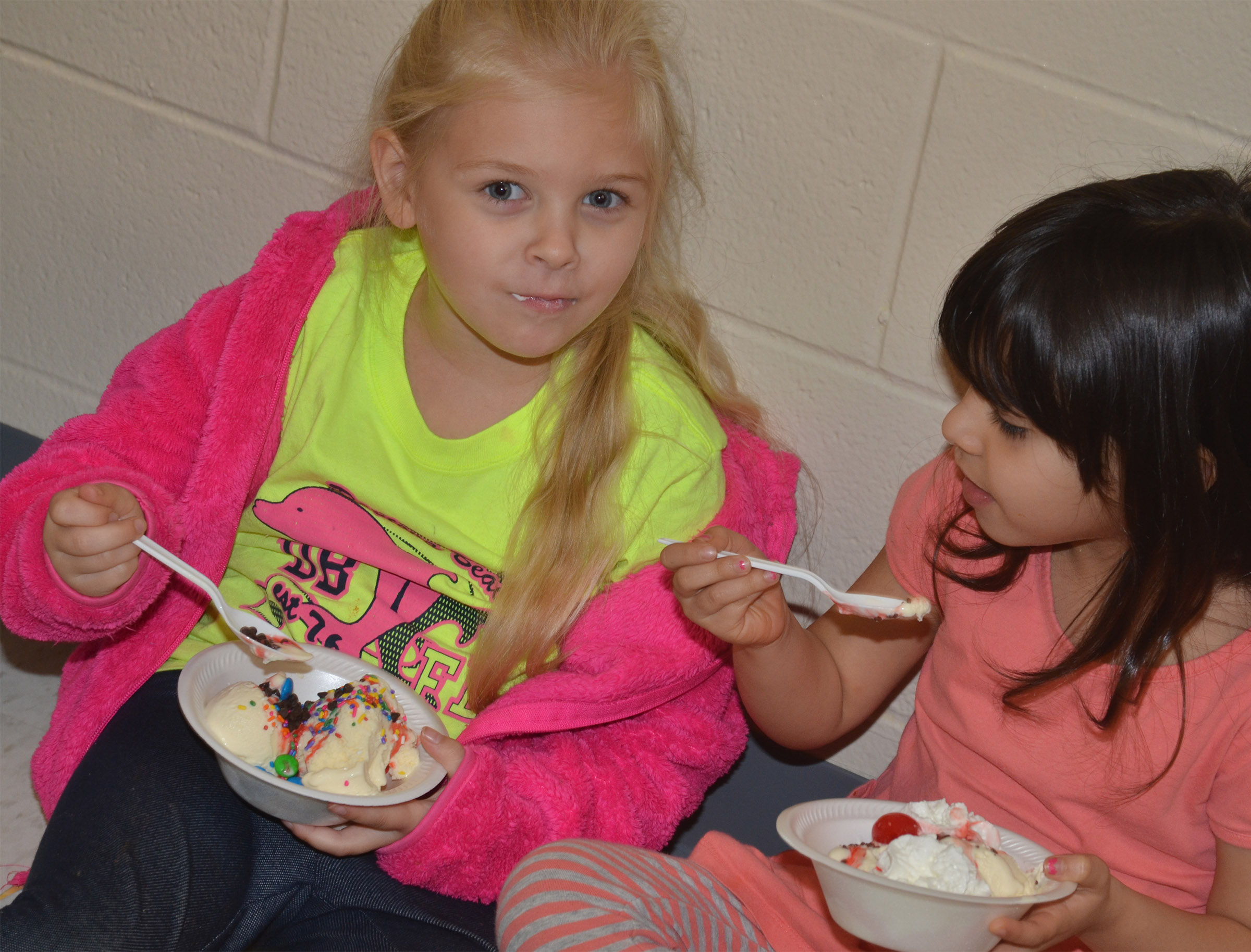 CES kindergarteners Aubrey Novak, at left, and Carol Moura talk as they enjoy their ice cream sundae.