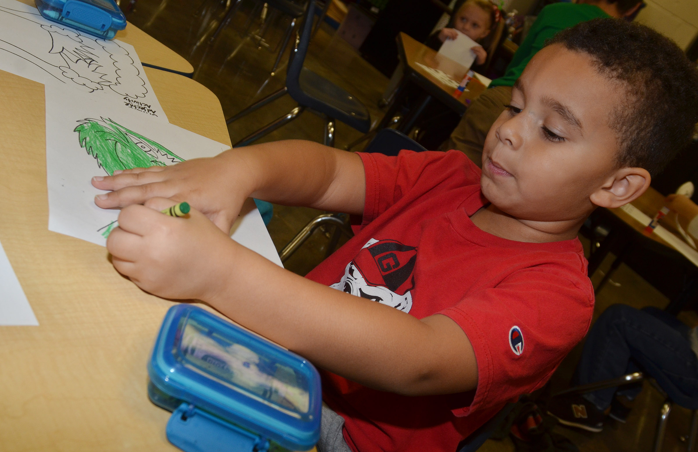 CES kindergartener Tyrek Moore colors the Grinch.