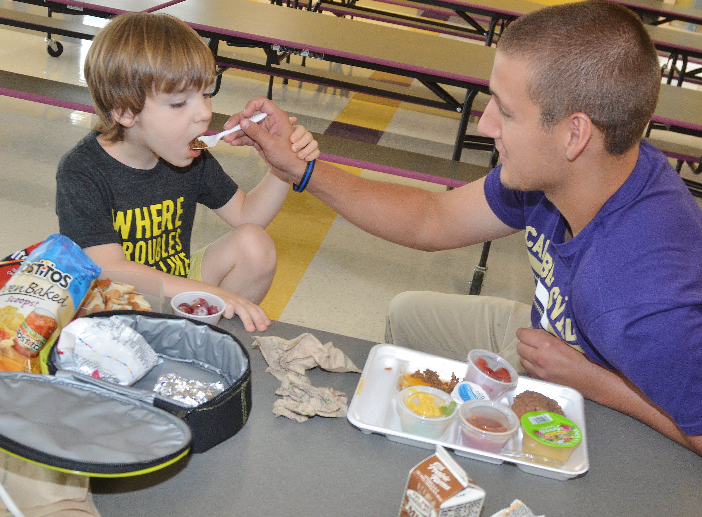CES Instructional Assistant Zach Durham helps kindergartener Finley Williams eat his lunch.