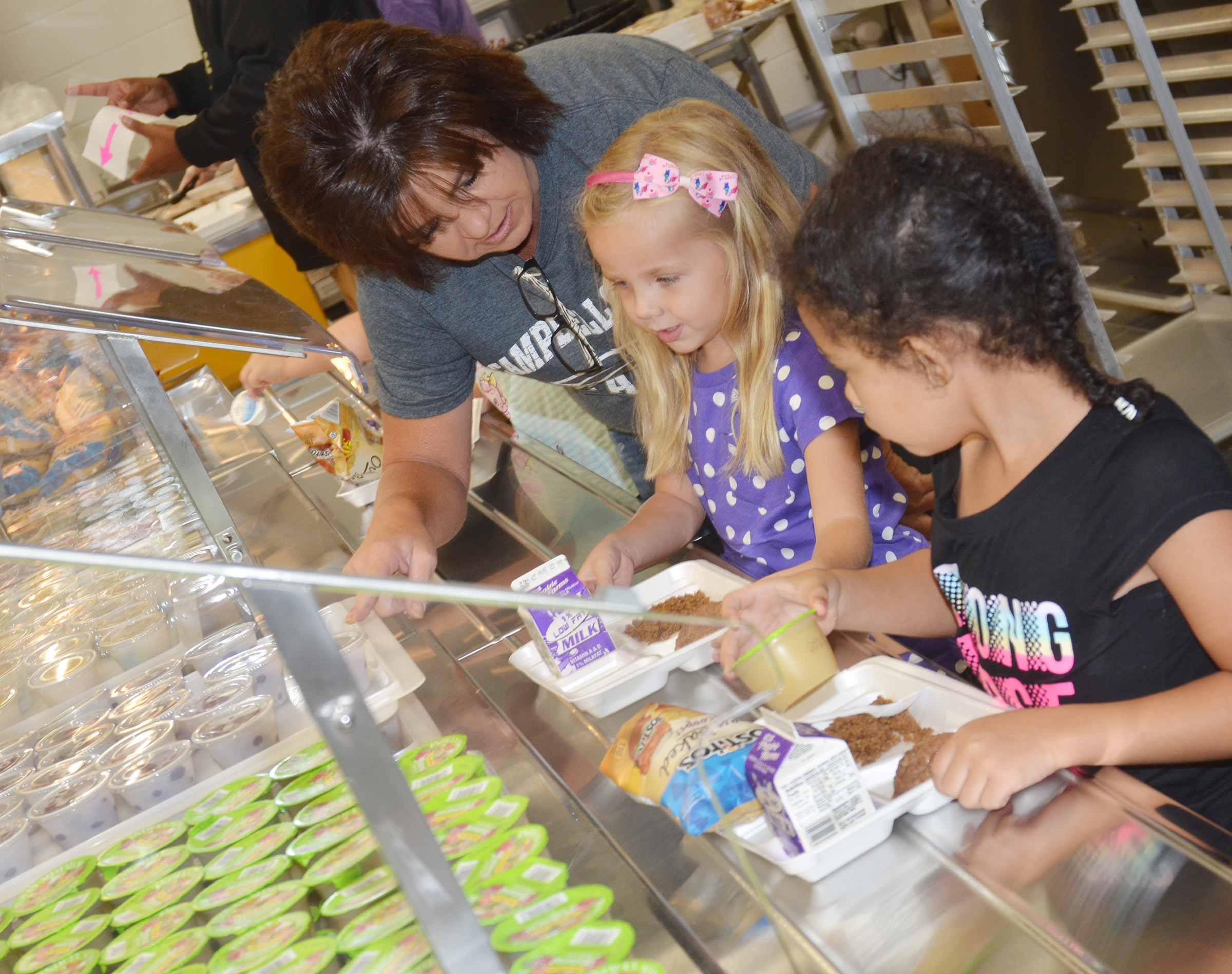 CES cafeteria worker Shelly Wilson helps kindergarteners Trinidy Gribbins, center, and Rylee Karr select what they want to eat.