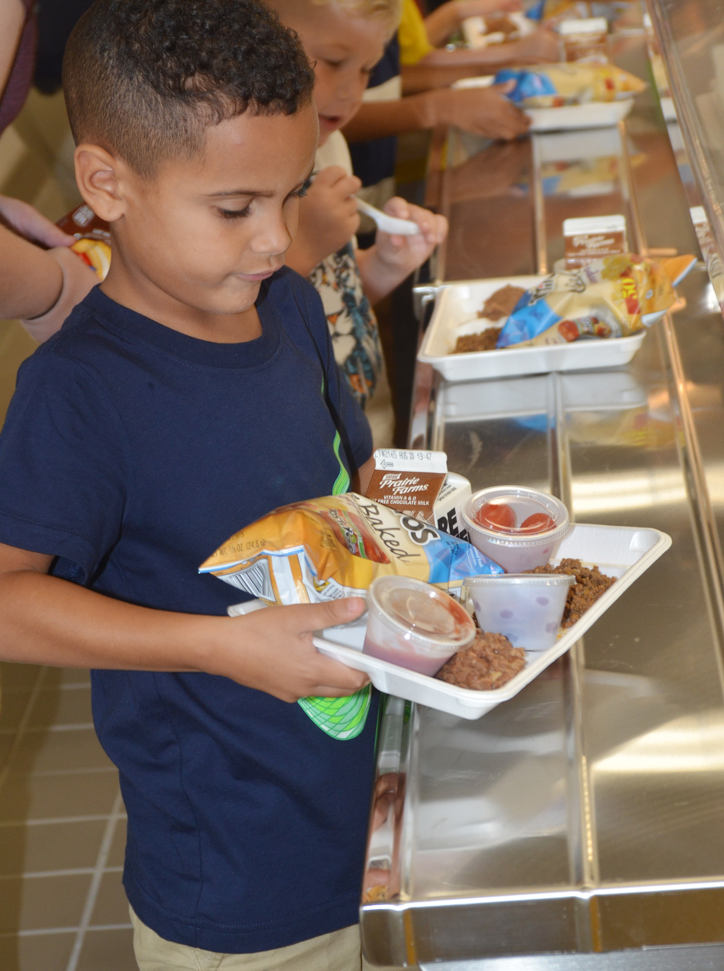 CES kindergartener Kingston Cowherd carries his tray.