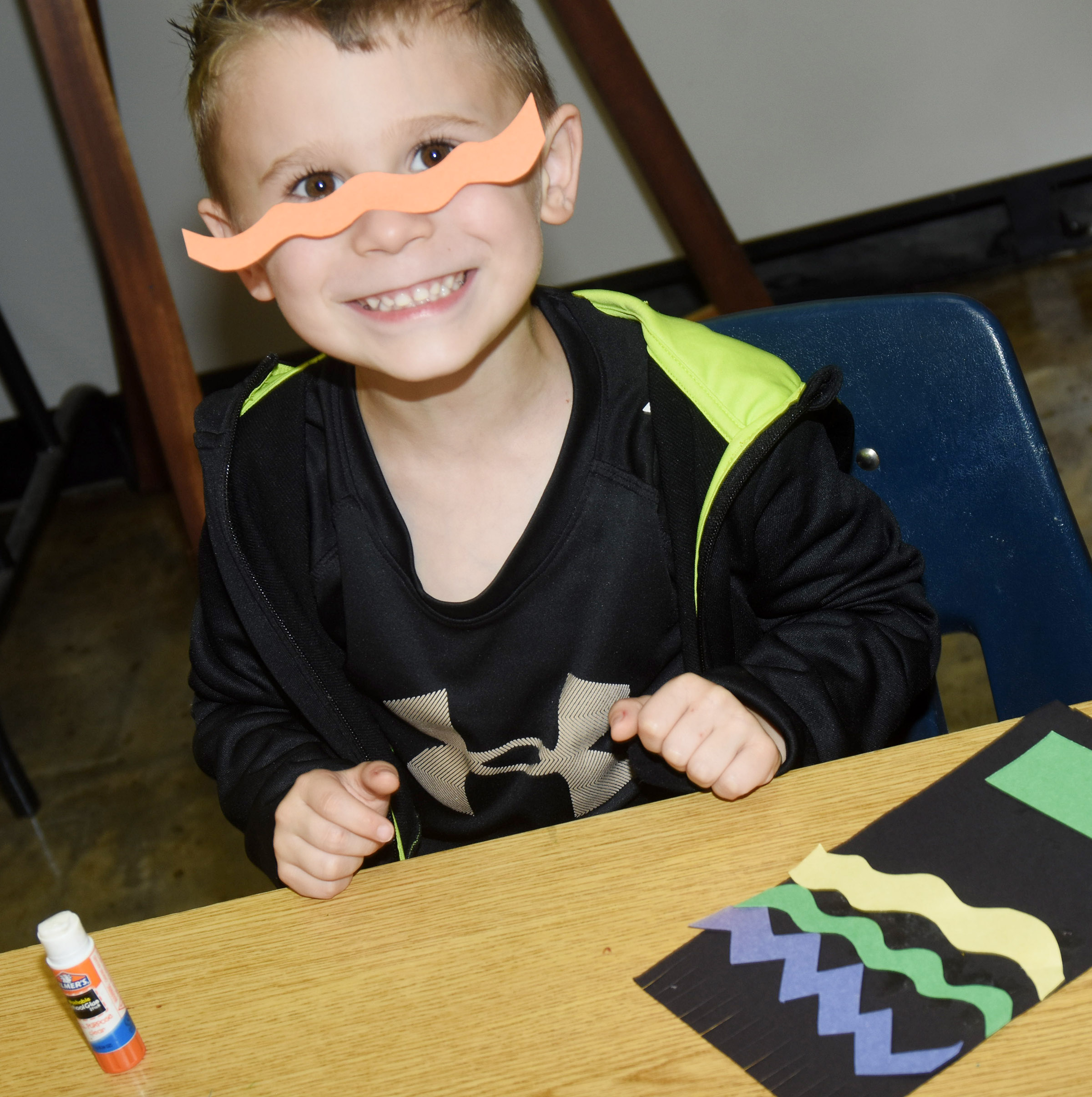CES kindergartener Karson Wright glues a line on his face.