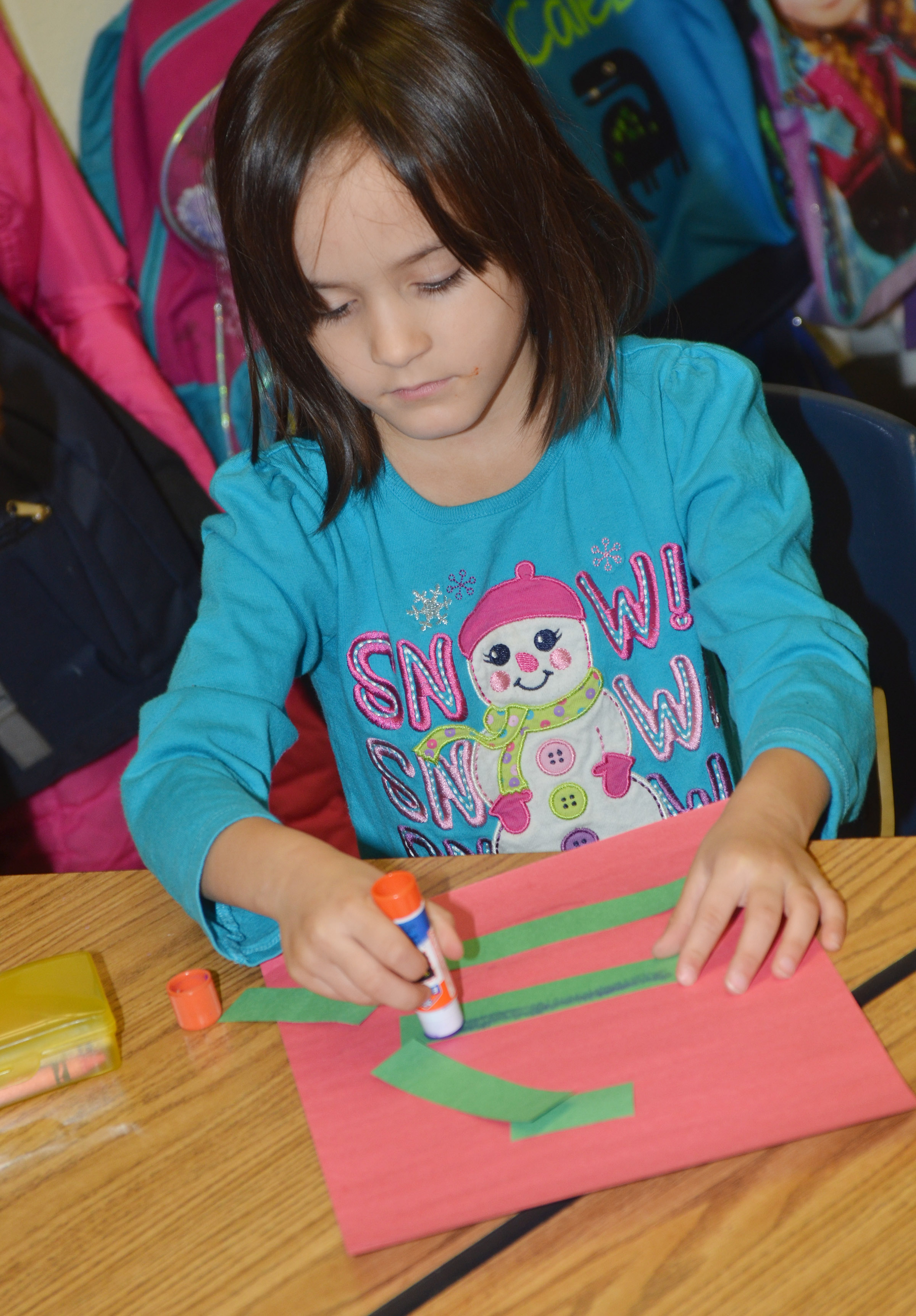 CES kindergartener Jo Jo Bledsoe glues her Christmas tree together.