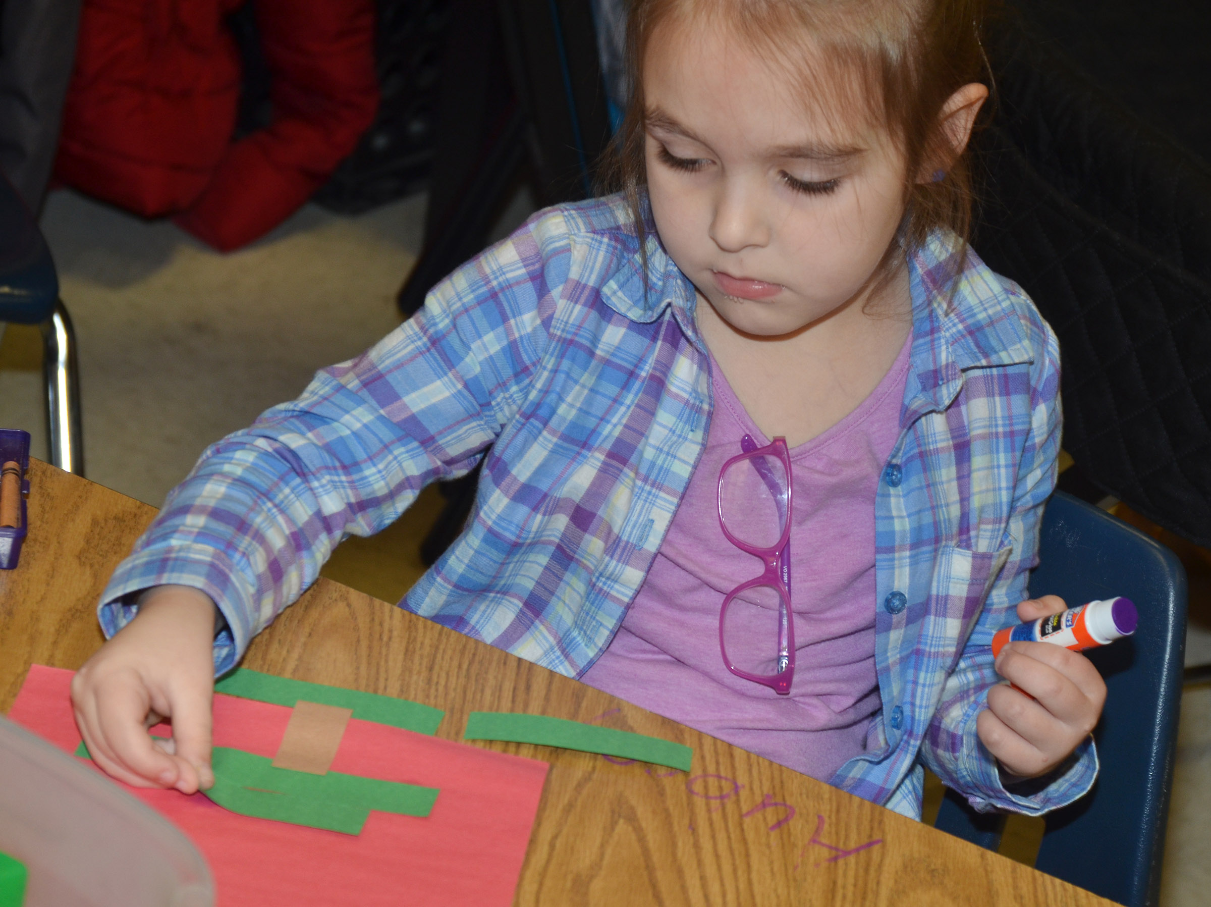 CES kindergartener Aubrey Allen glues her Christmas tree together.