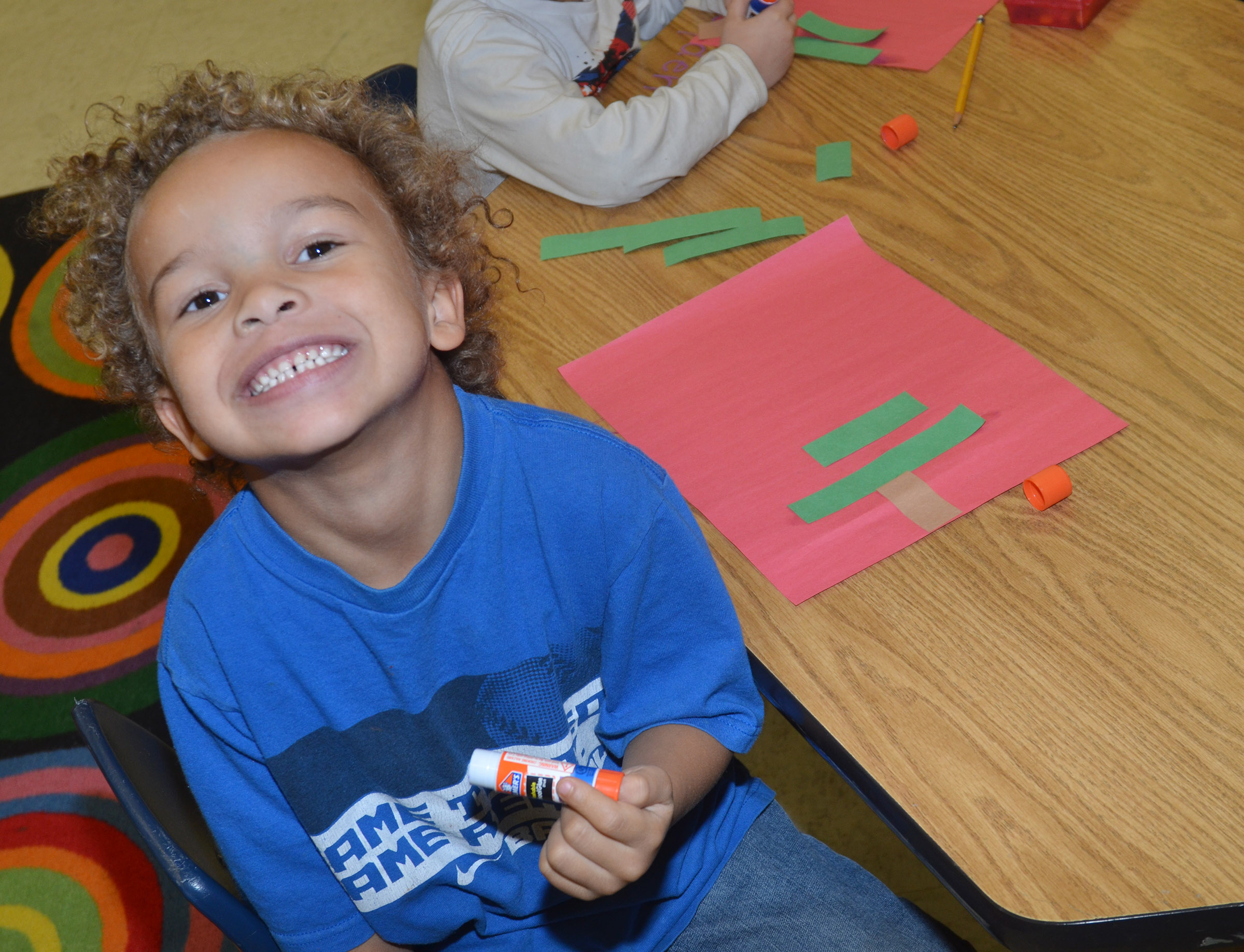 CES kindergartener Dyra Welch smiles as he glues his Christmas tree together.