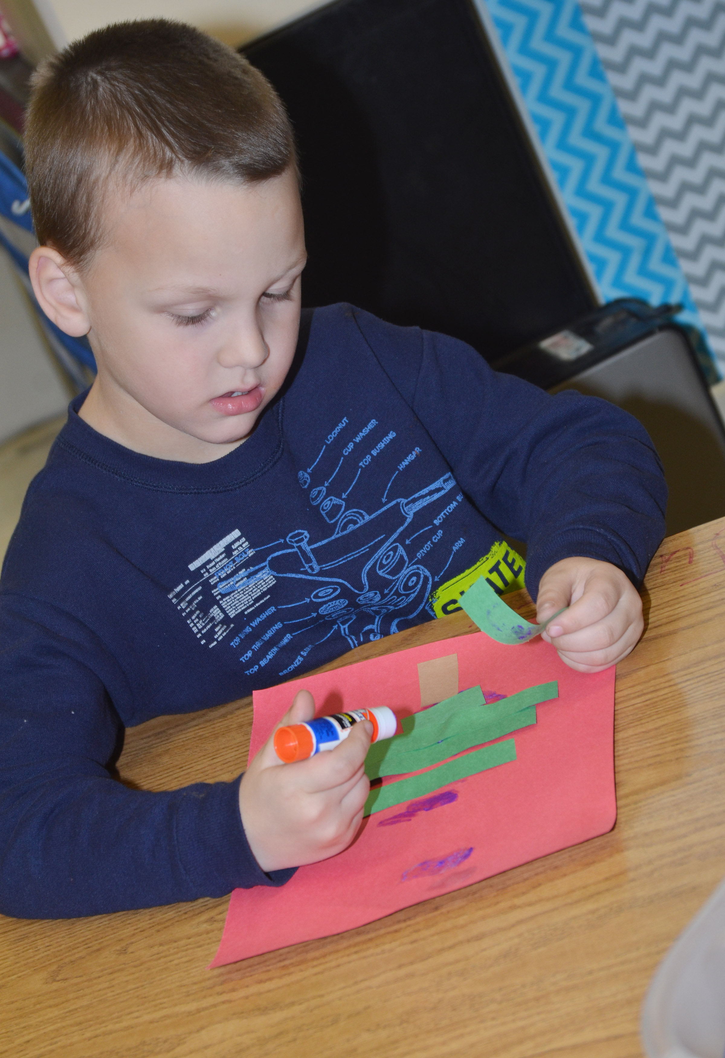 CES kindergartener Justice Nelson glues his Christmas tree together.