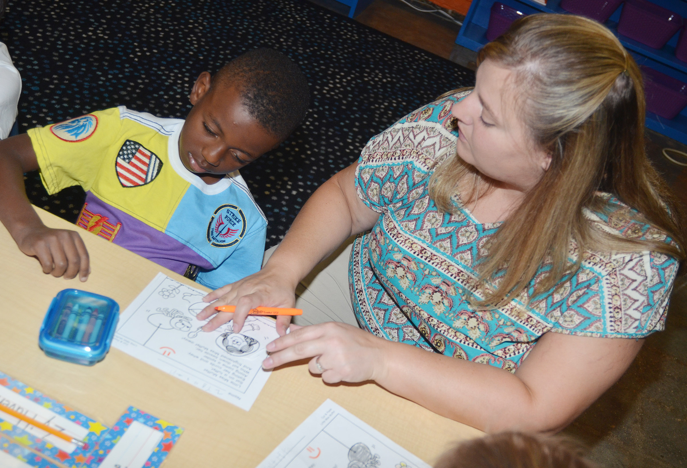 CES teacher Kimberly Clark helps kindergartener Zyhaven Taylor read Little Miss Muffet.