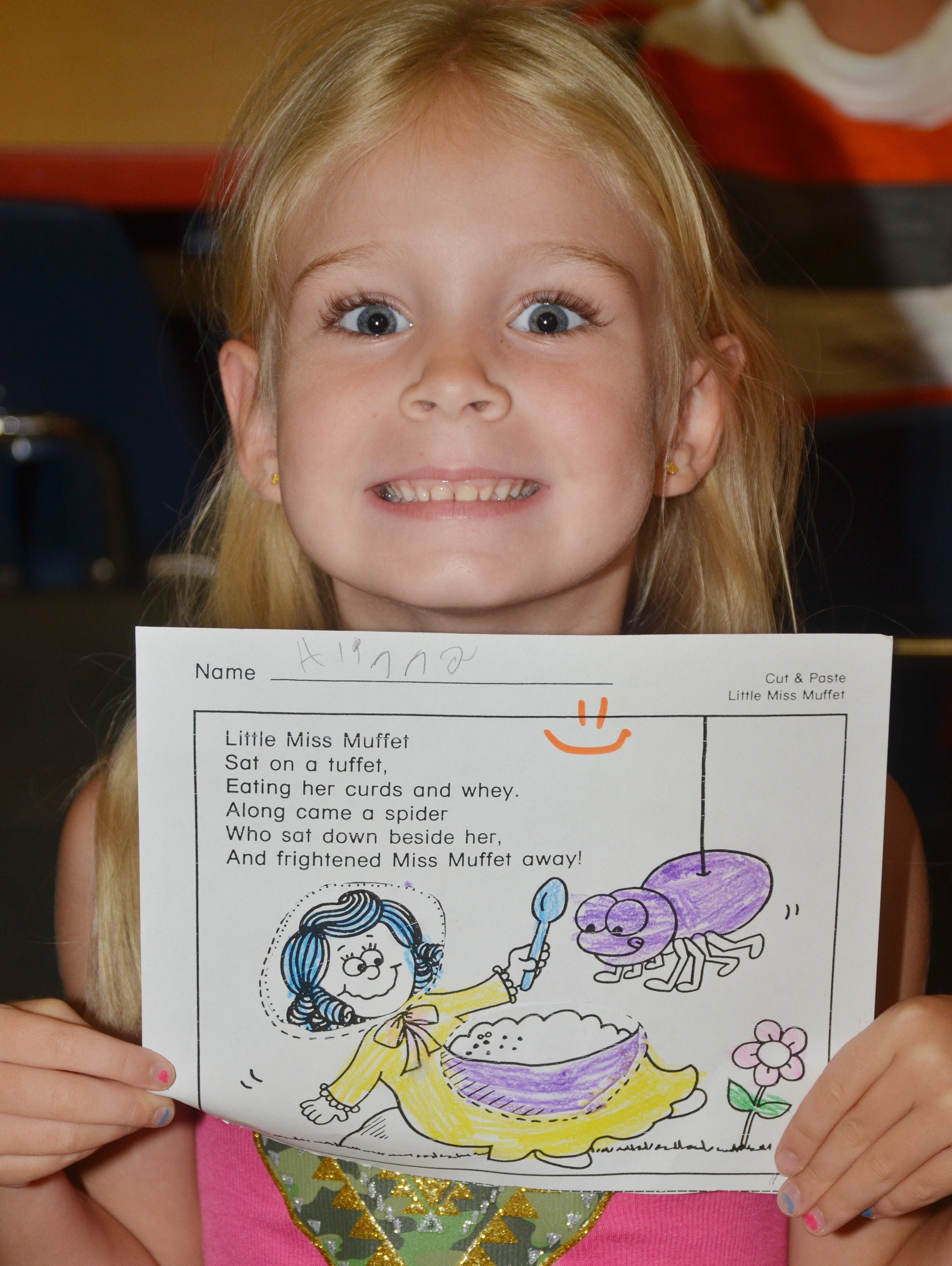 CES kindergartener Alinna Bray holds her finished Little Miss Muffet worksheet.