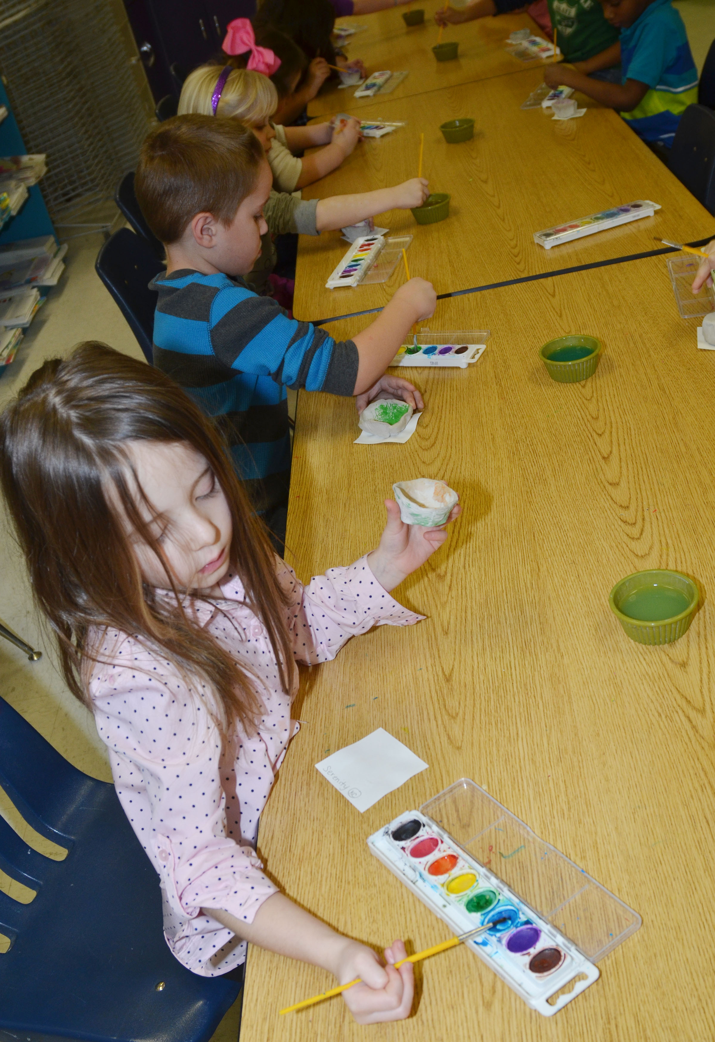 CES kindergartener Serenity Bell paints her pinch pot.