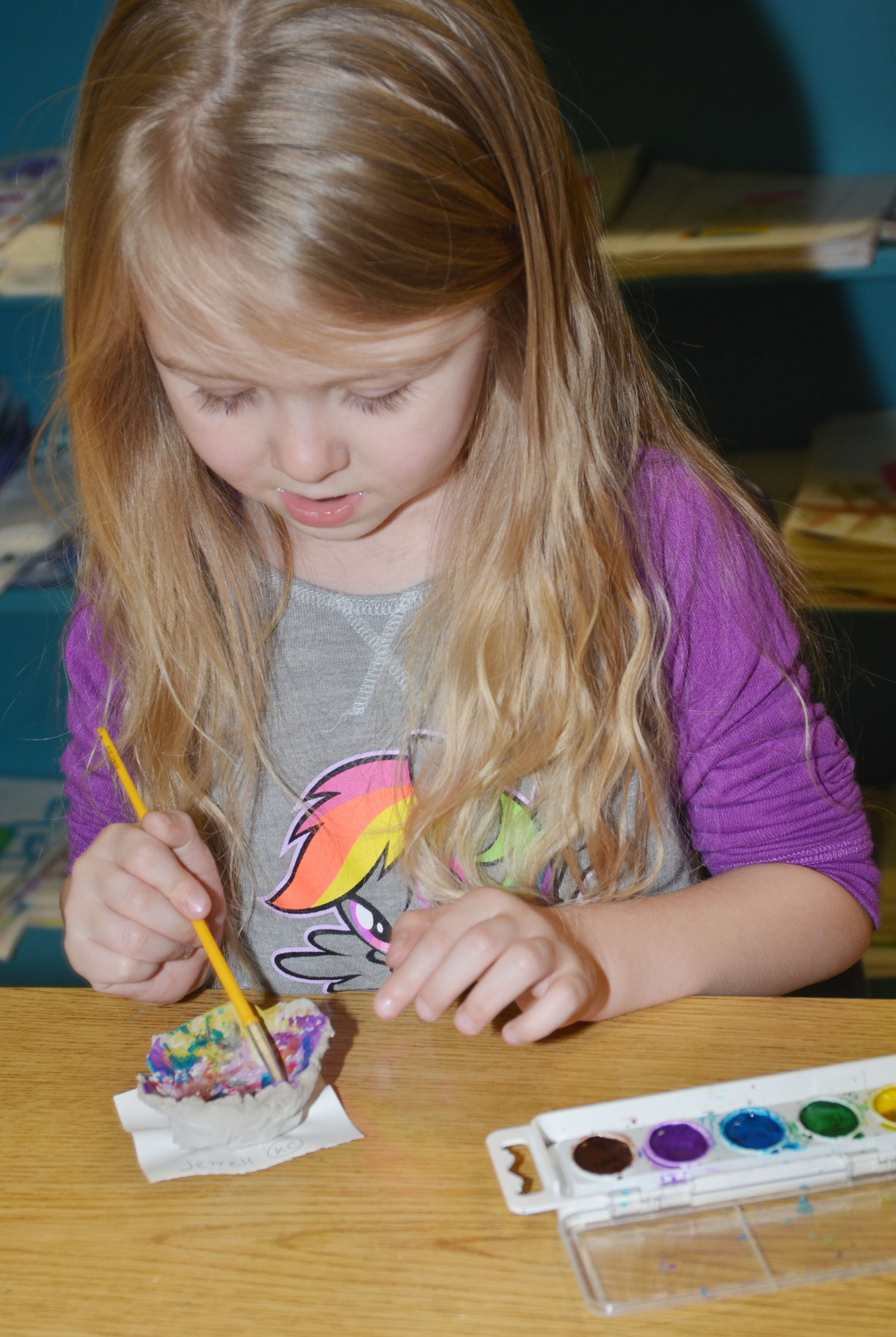CES kindergartener Jewell Brewster paints her pinch pot.