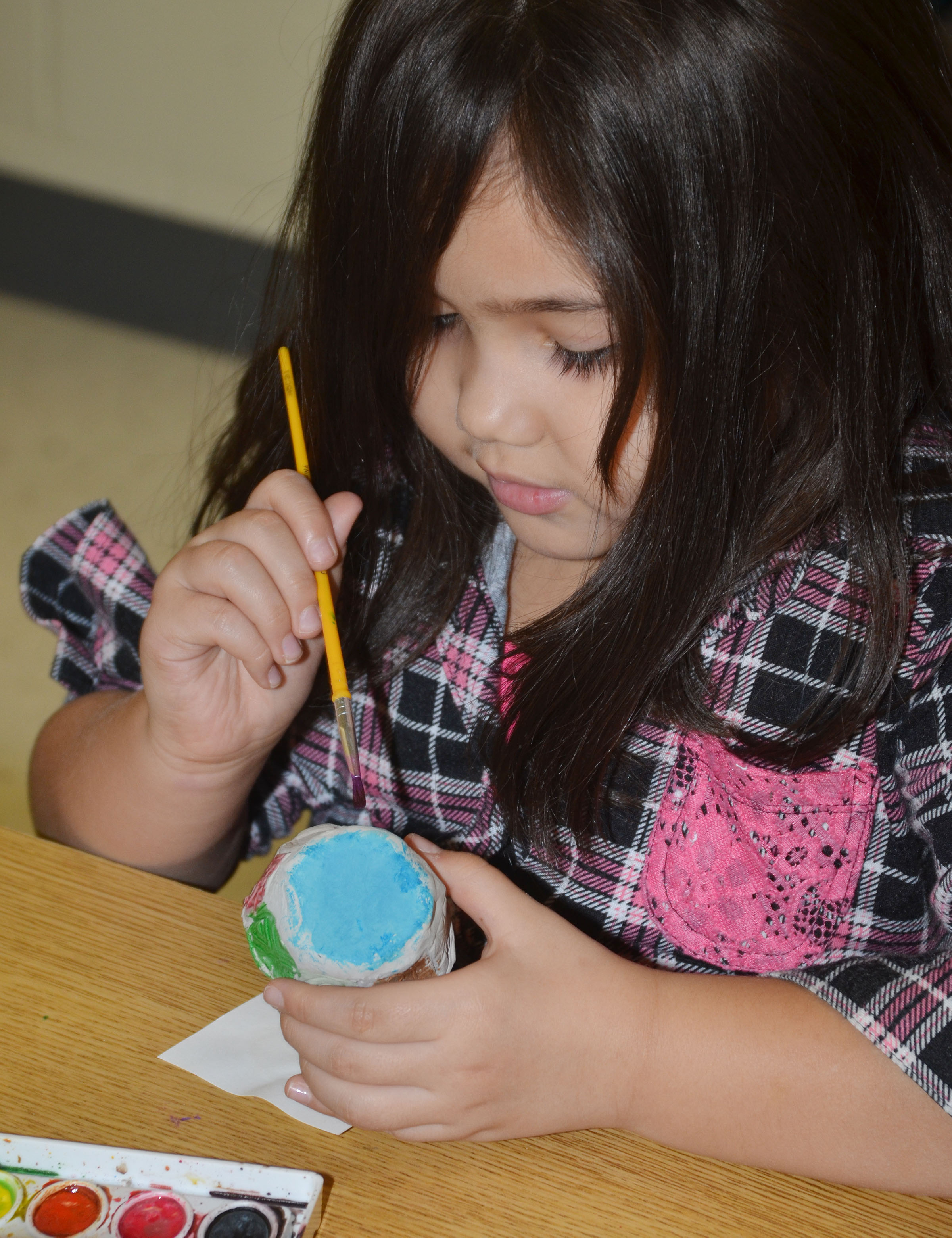 CES kindergartener Hannah Matias paints her pinch pot.