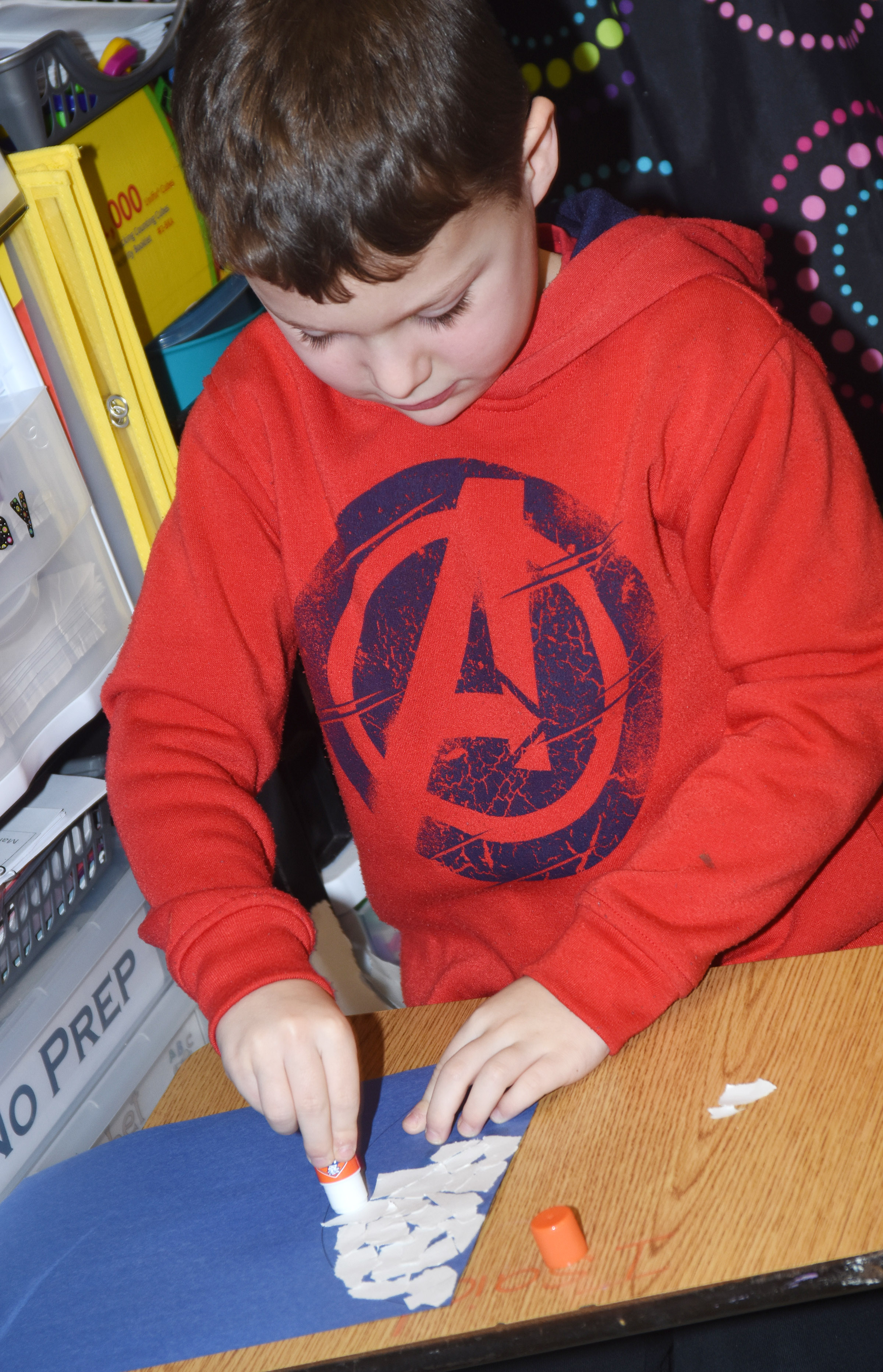 CES kindergartener Kyler Wilson glues together construction paper to make his snowman.