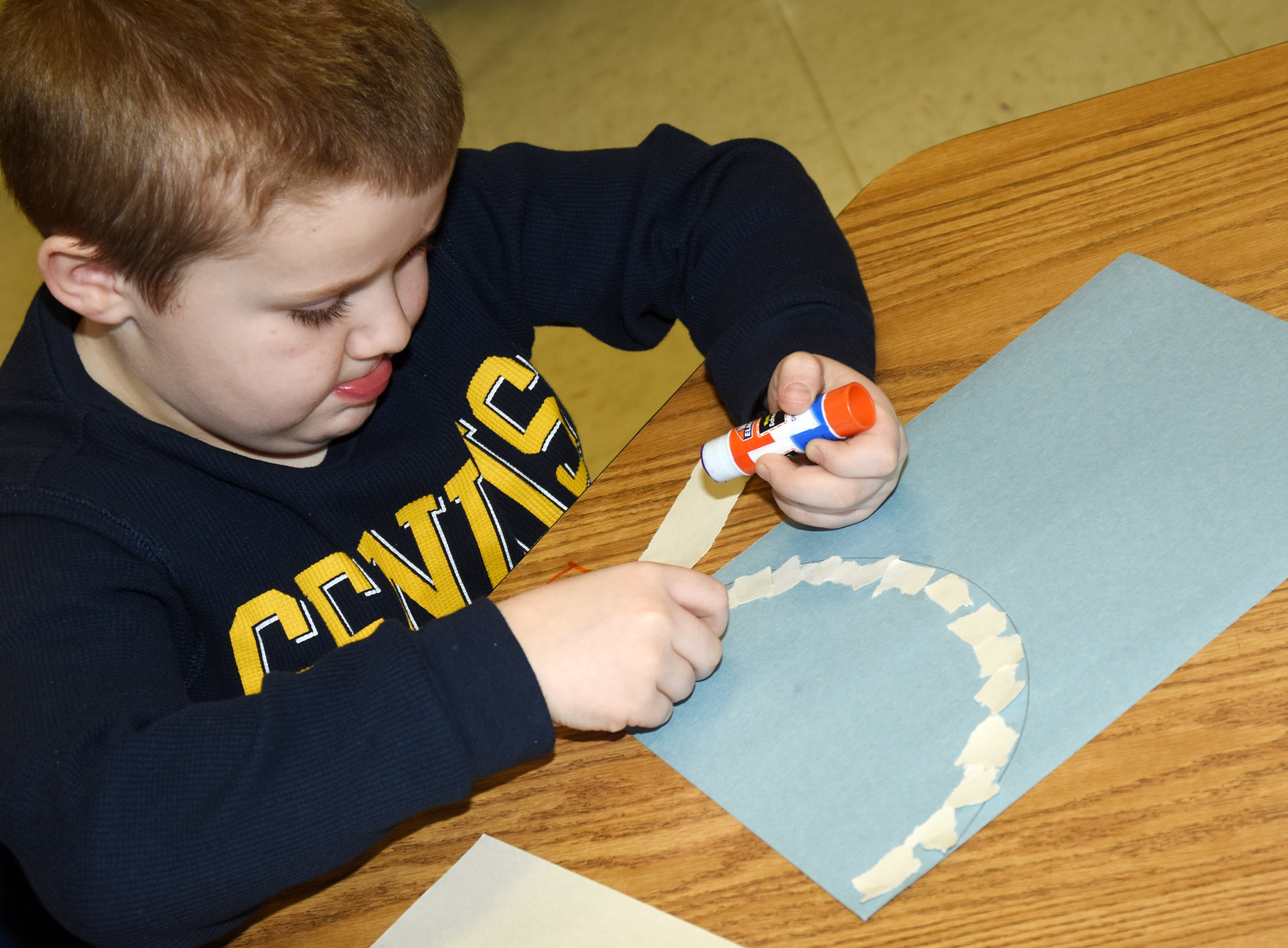 CES kindergartener Levi Dye glues together construction paper to make his snowman.