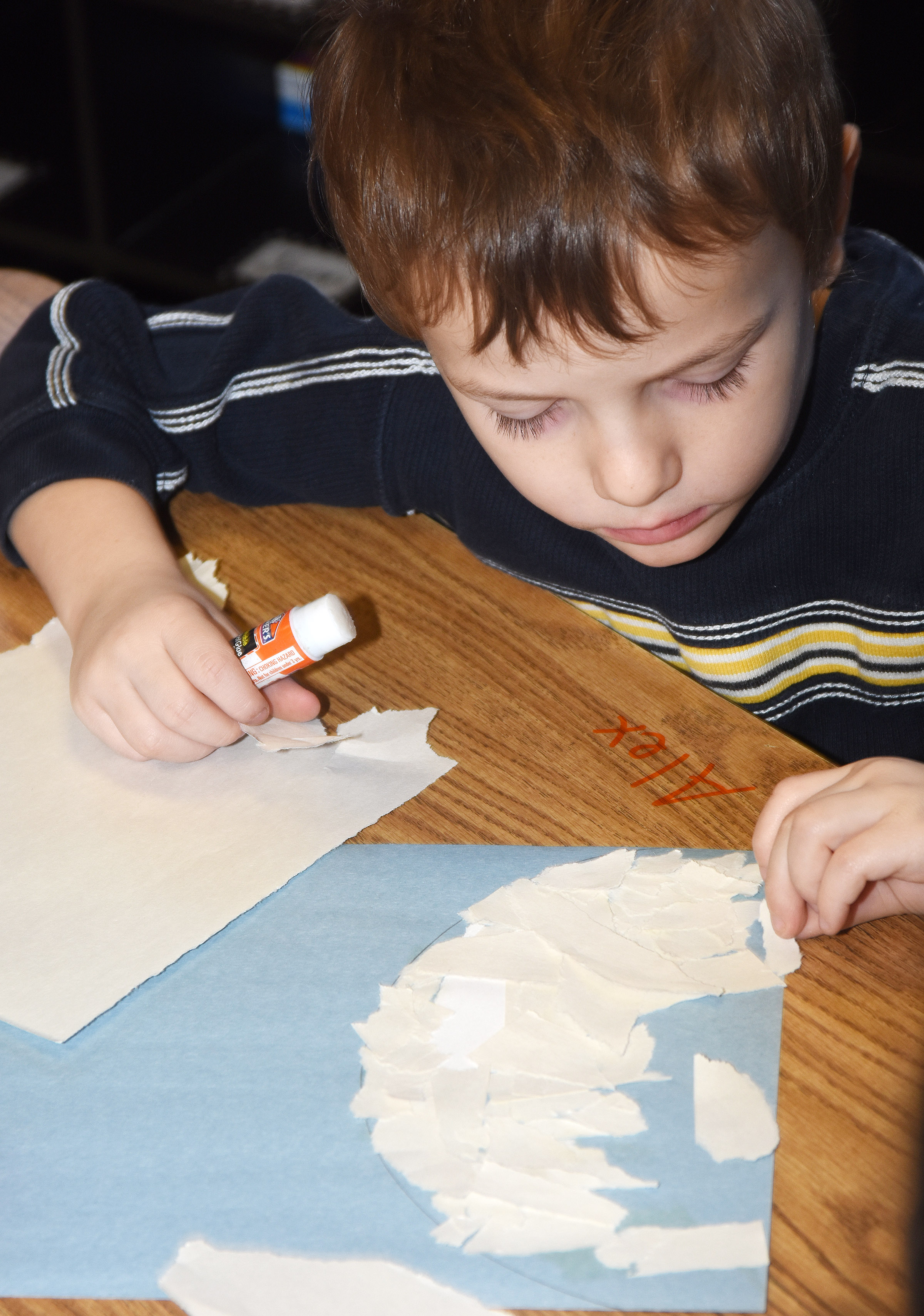 CES kindergartener Brayden Carmicle glues together construction paper to make his snowman.