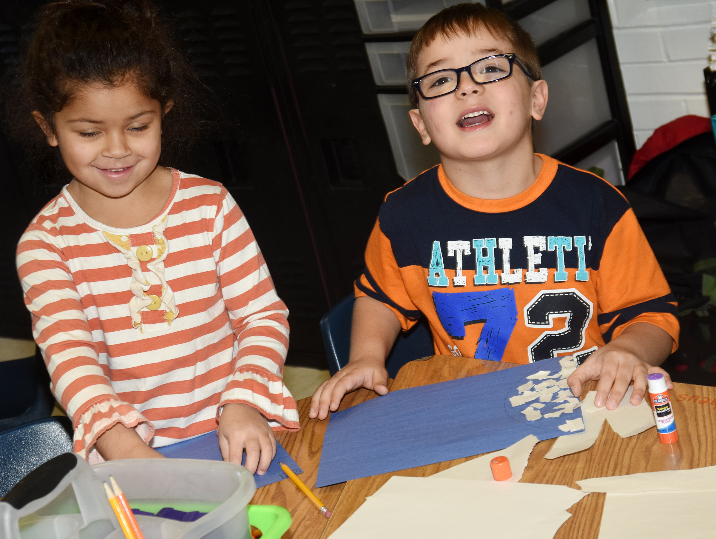 CES kindergarteners Amiiyah Nunez, at left, and Matheus Almeida glue together construction paper as they make their snowmen.