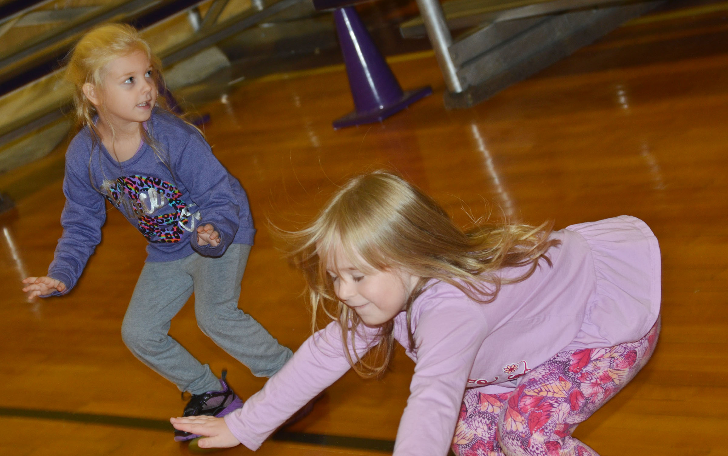 CES kindergarteners Aubrey Novak, at right, and Briley Sapp stretch before they practice dribbling.