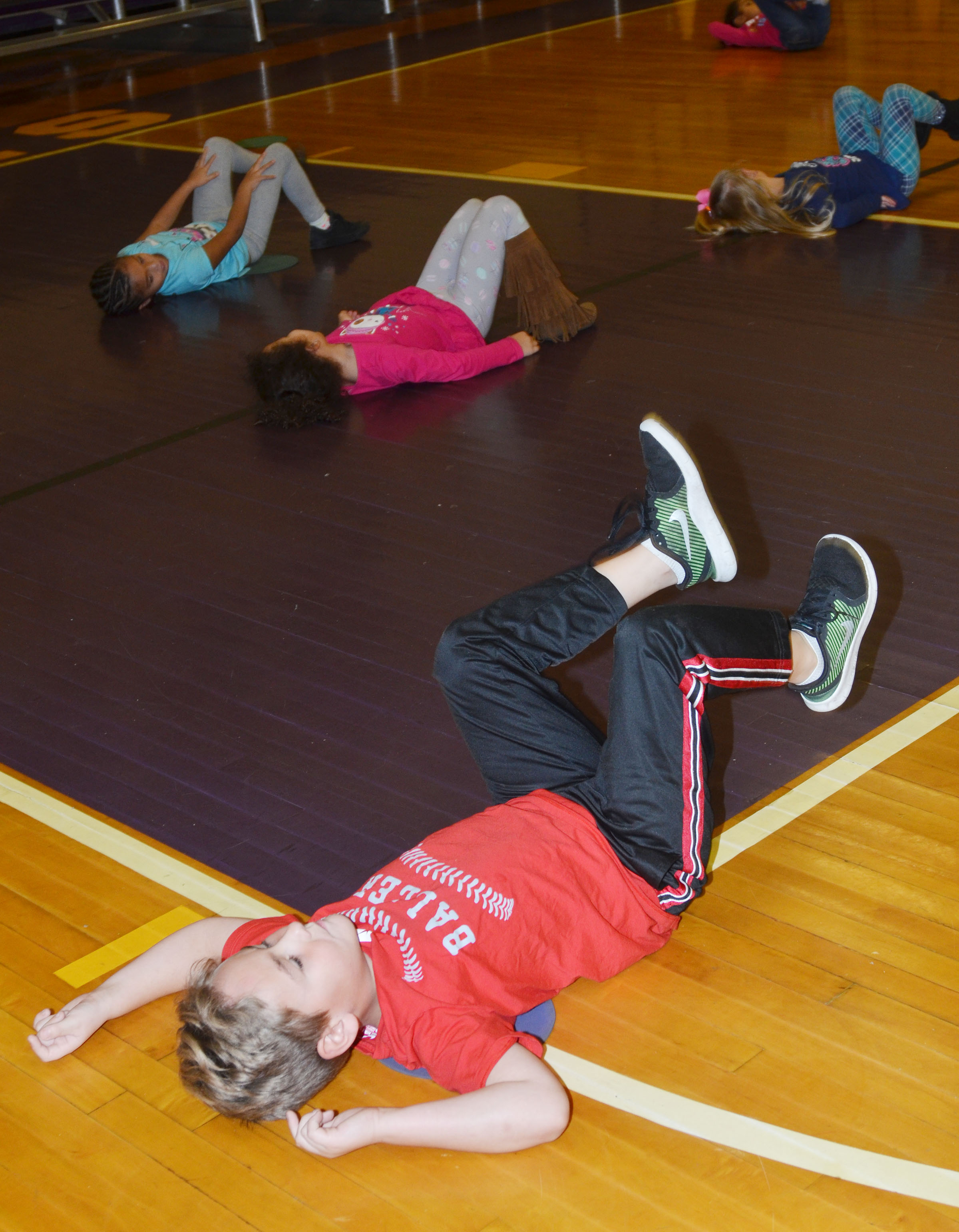 CES kindergartener Braxton Rhodes and his classmates do some exercises before they practice their dribbling.
