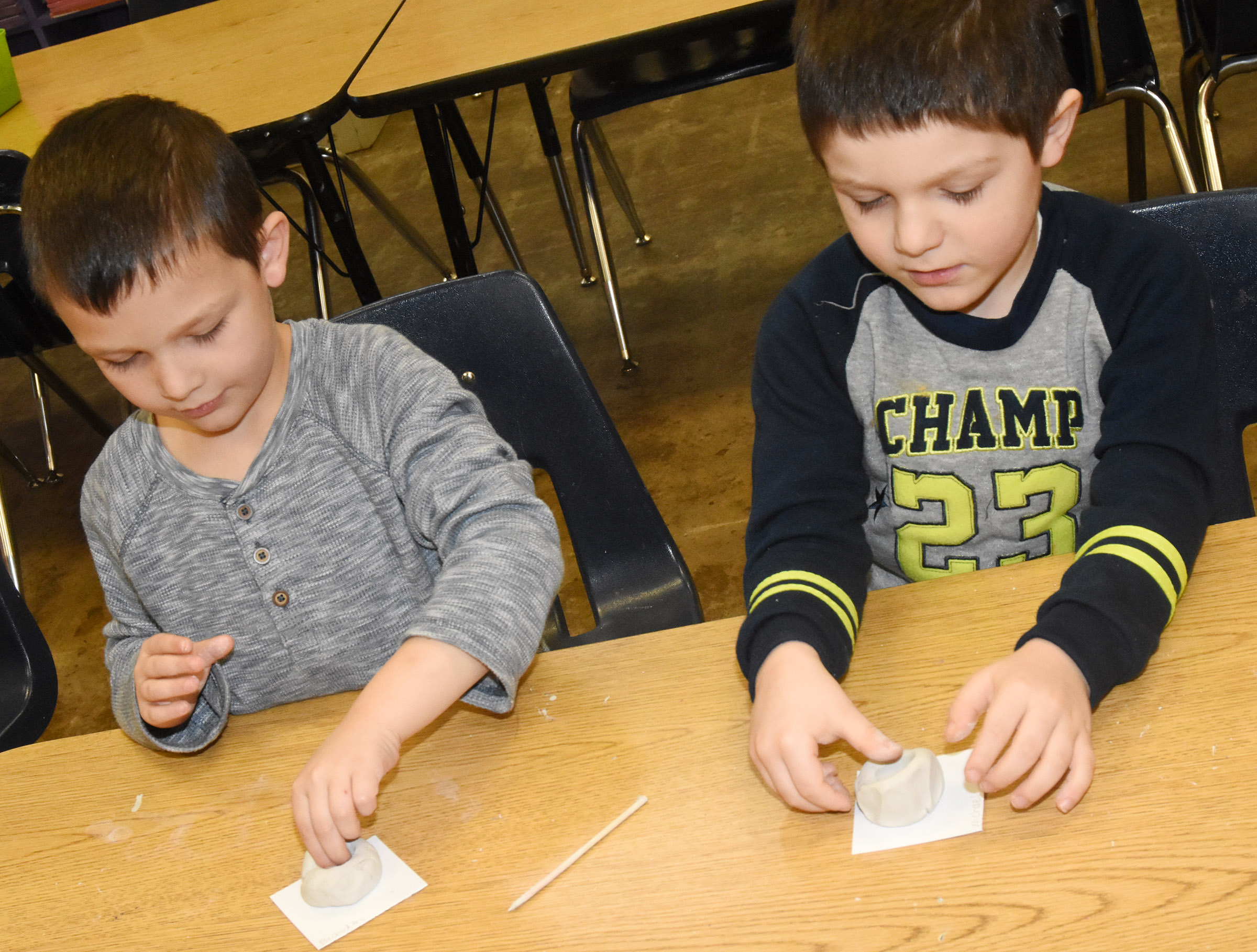 CES kindergarteners Brayden Perkins, at left, and Michael Priddy place their thumbs in their clay to make their pinch pots.
