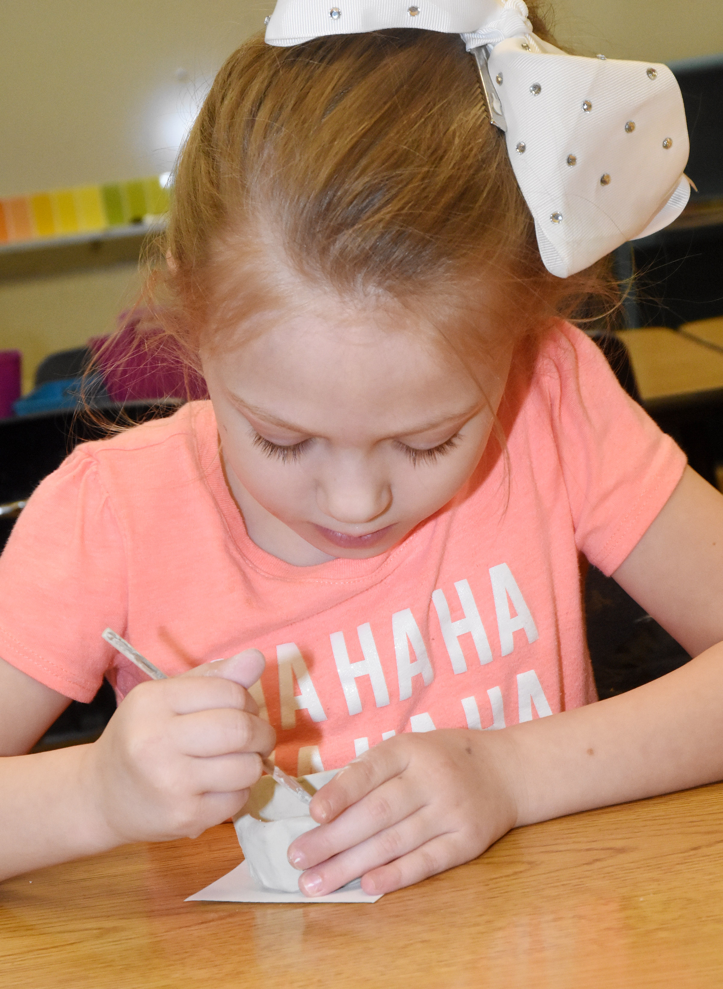 CES kindergartener Amary Tompkins adds texture to her pinch pot.