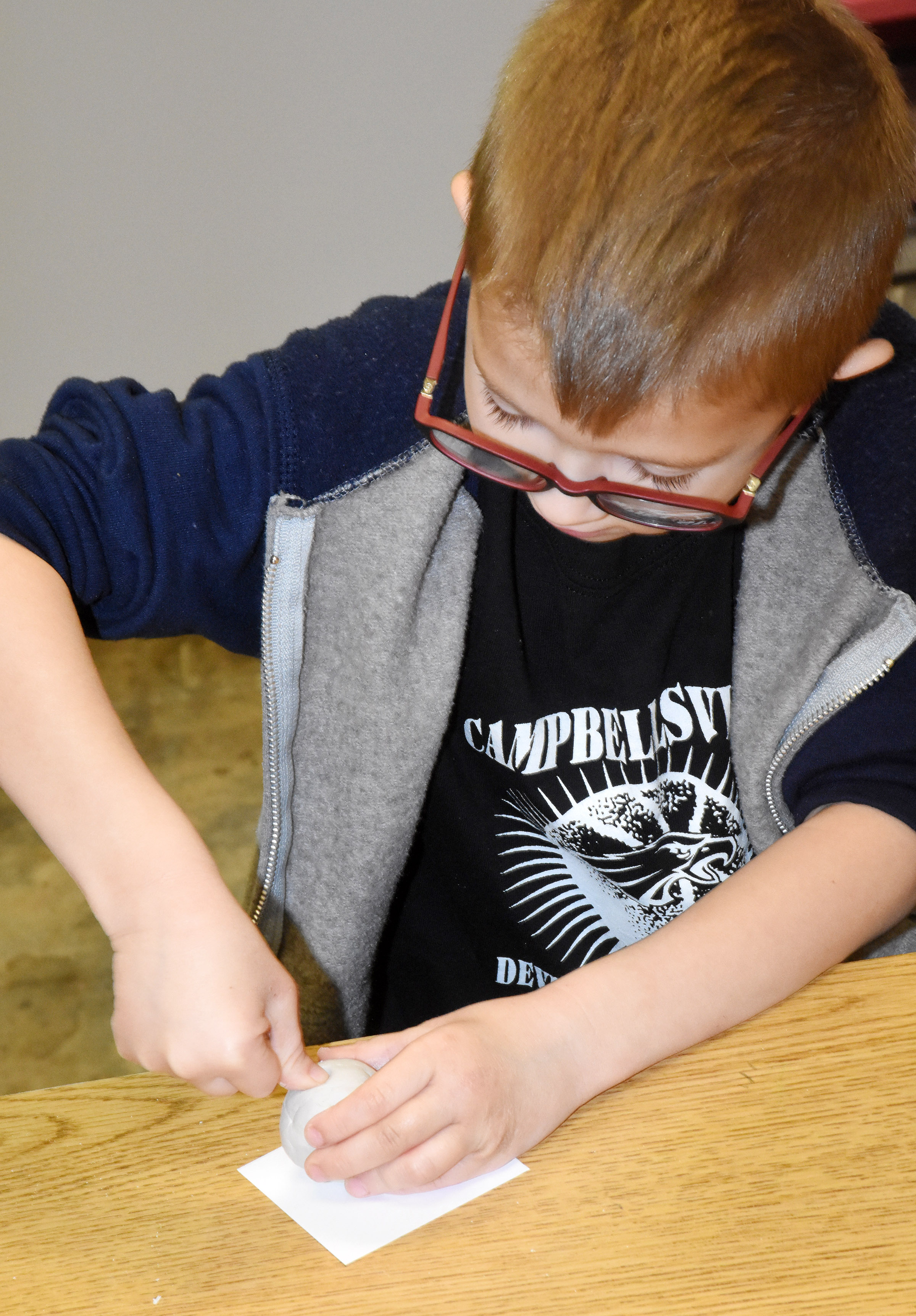 CES kindergartener Andrew Stout places his thumb in his clay to make his pot.