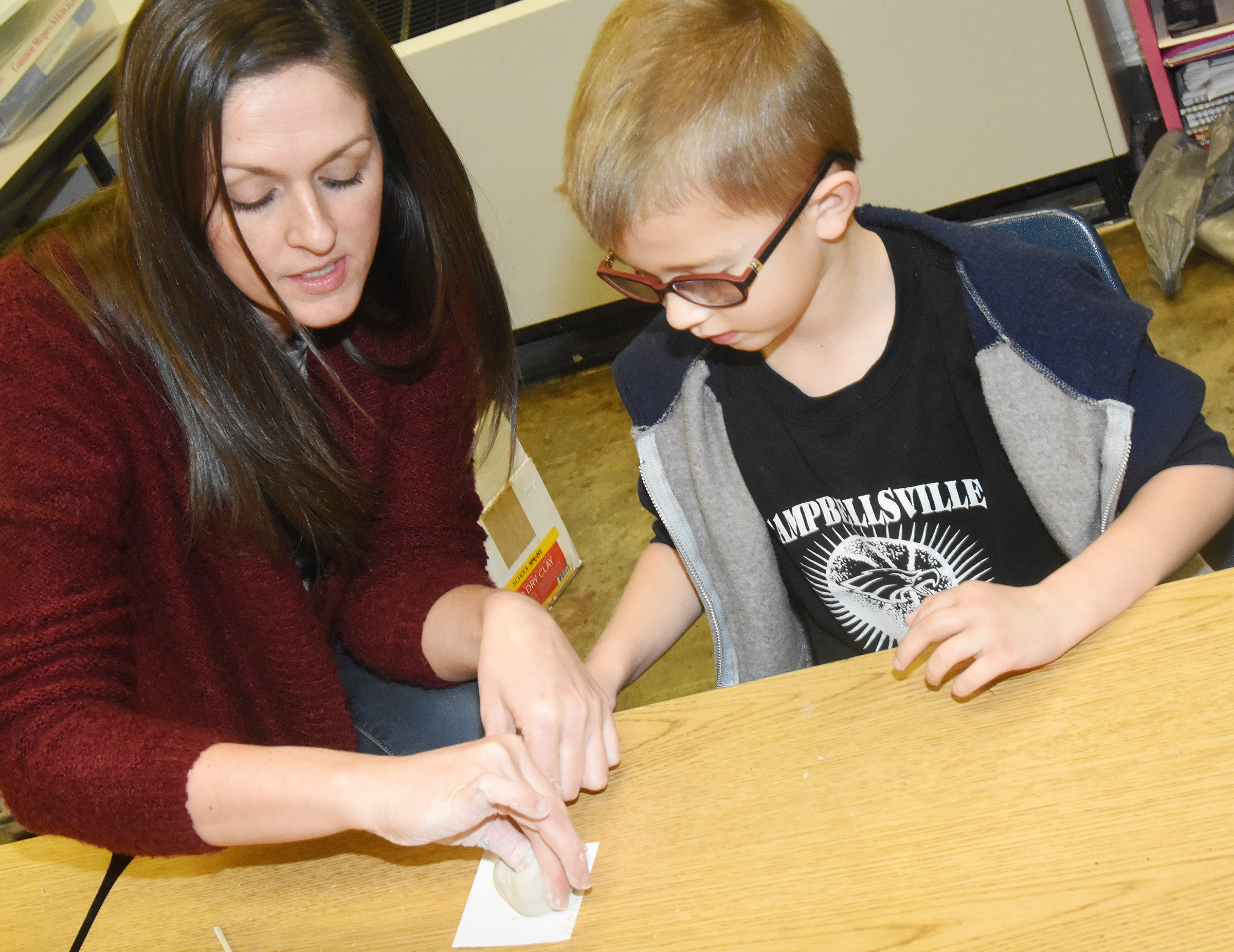 CES art teacher Adrienne Hash helps kindergartener Andrew Stout as he forms his pinch pot.