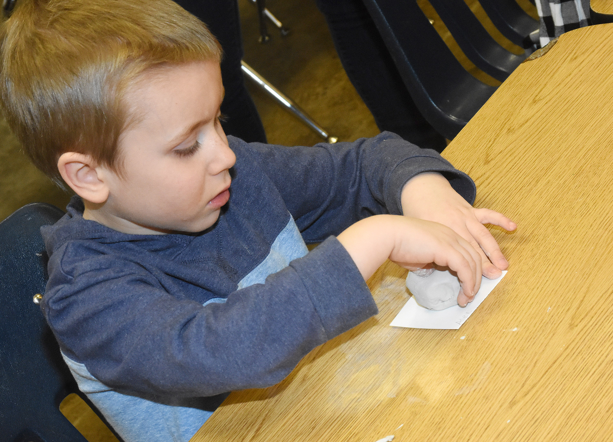 CES kindergartener Alex Newcomb places his thumb in his clay to make his pot.