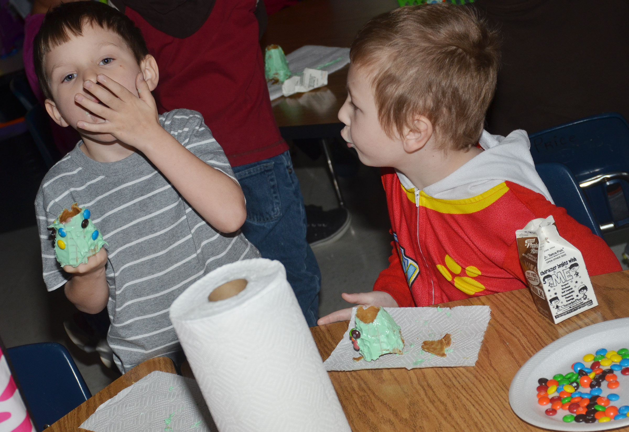 CES kindergarteners Shannon Carmicle, at left, and Cameron Dean enjoy their edible Christmas trees.