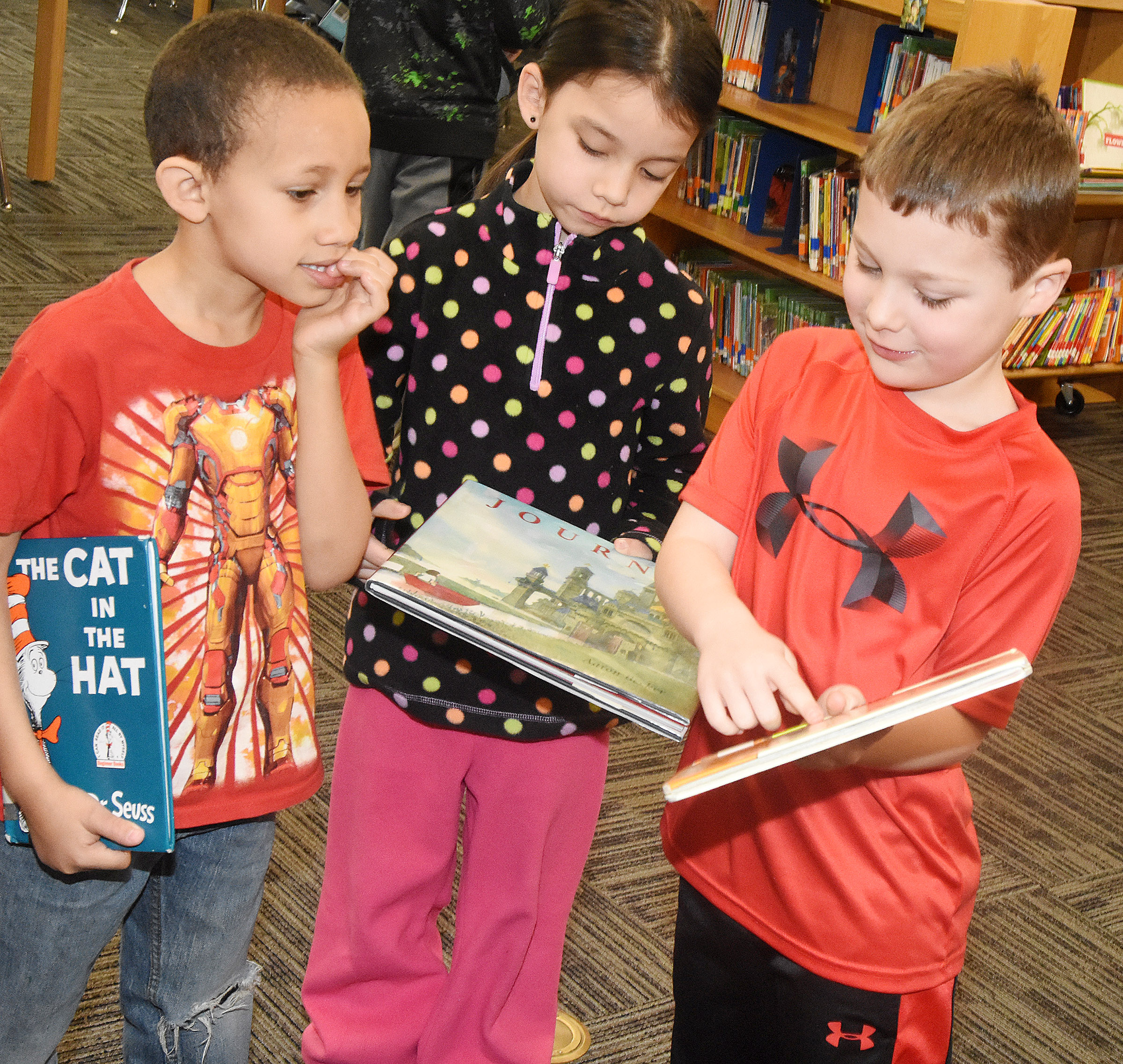 CES kindergartener Kyler Wilson shows his new book to classmates Jaxon Williams, at left, and Nevaeh Agent.