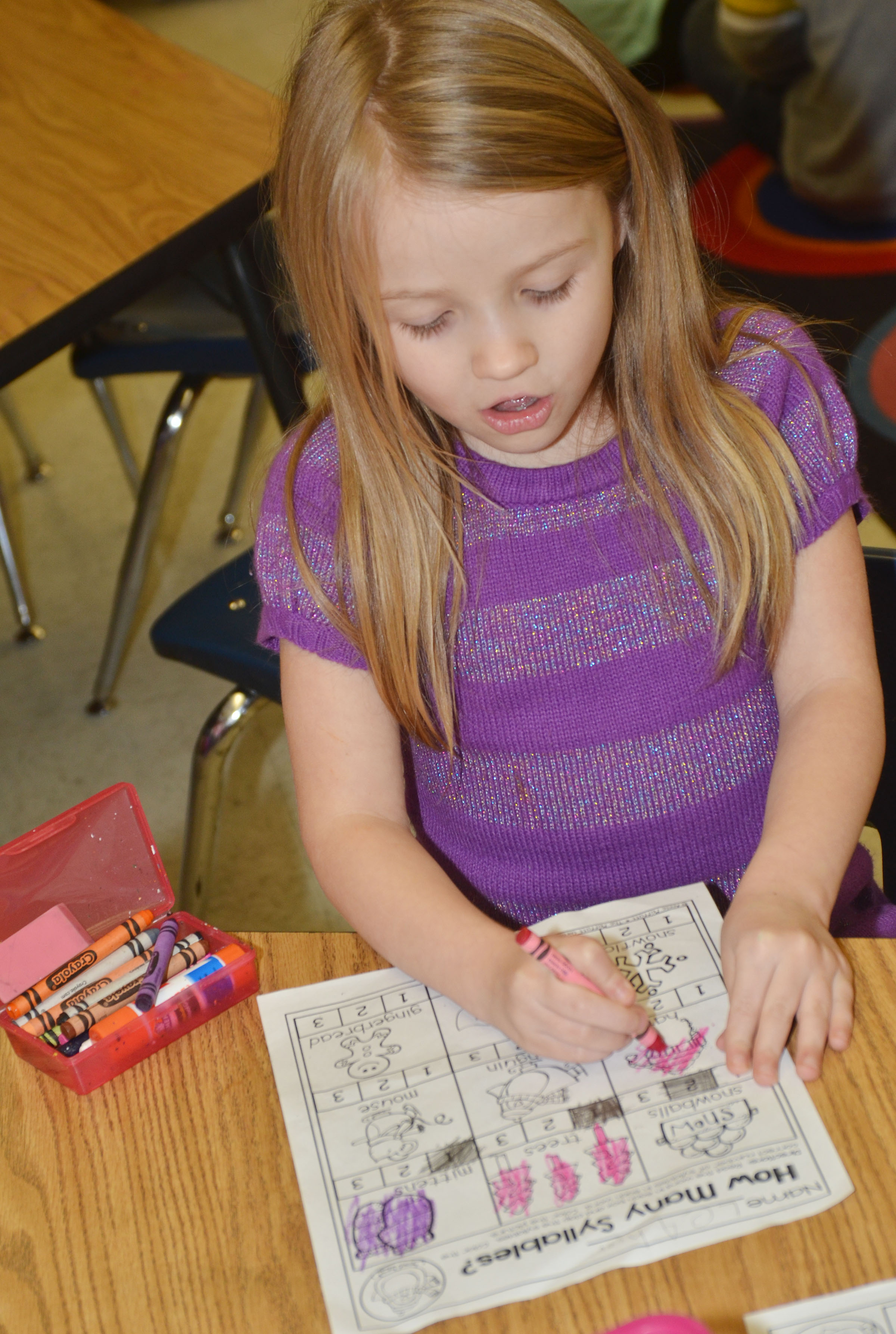 CES kindergartener Leah Covey colors her math worksheet.