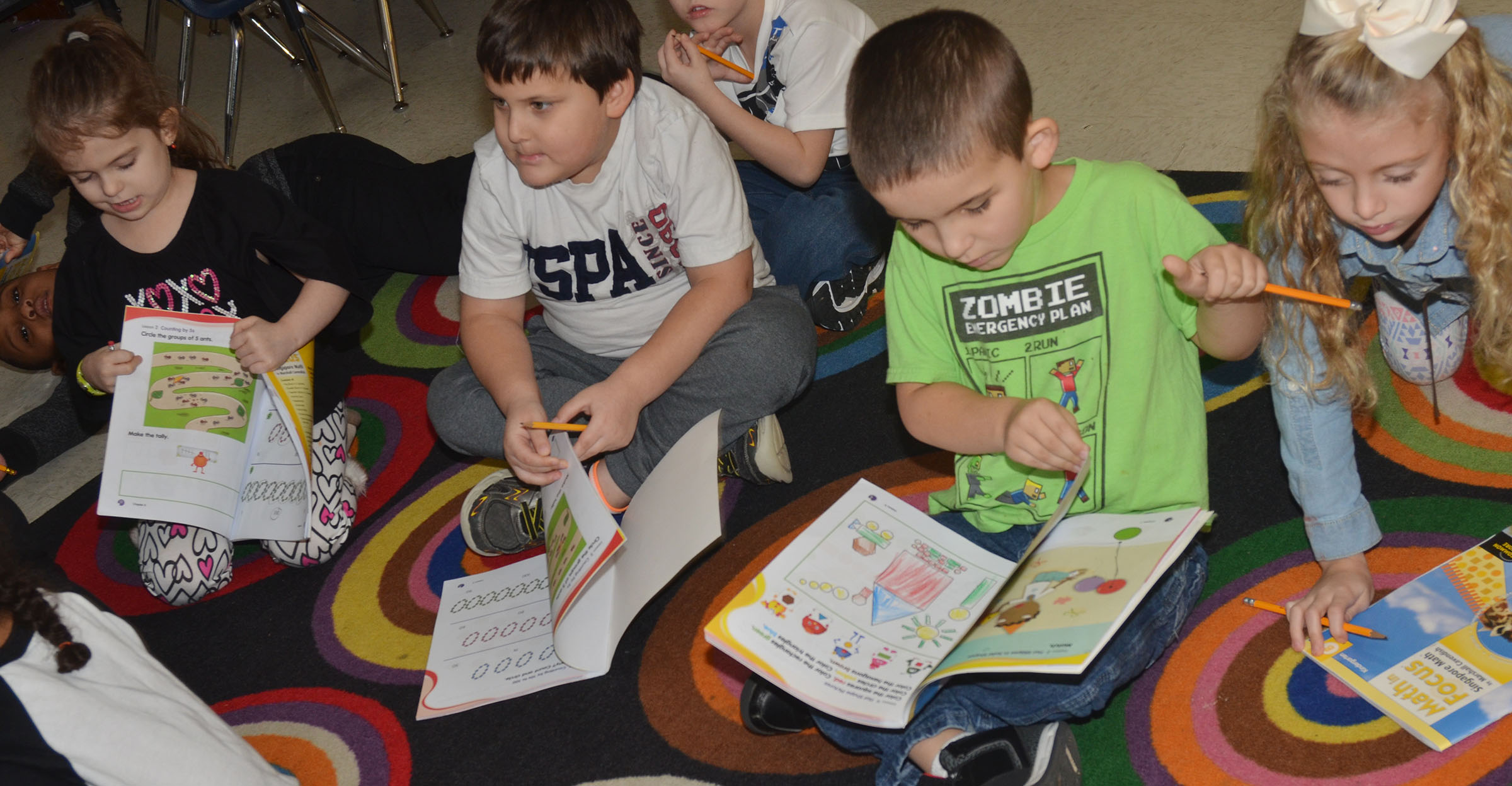 CES kindergarteners, from left, Addison Beckley, Cloud Malone, Mason Edwards and Aliyah Litsey work in their math books.