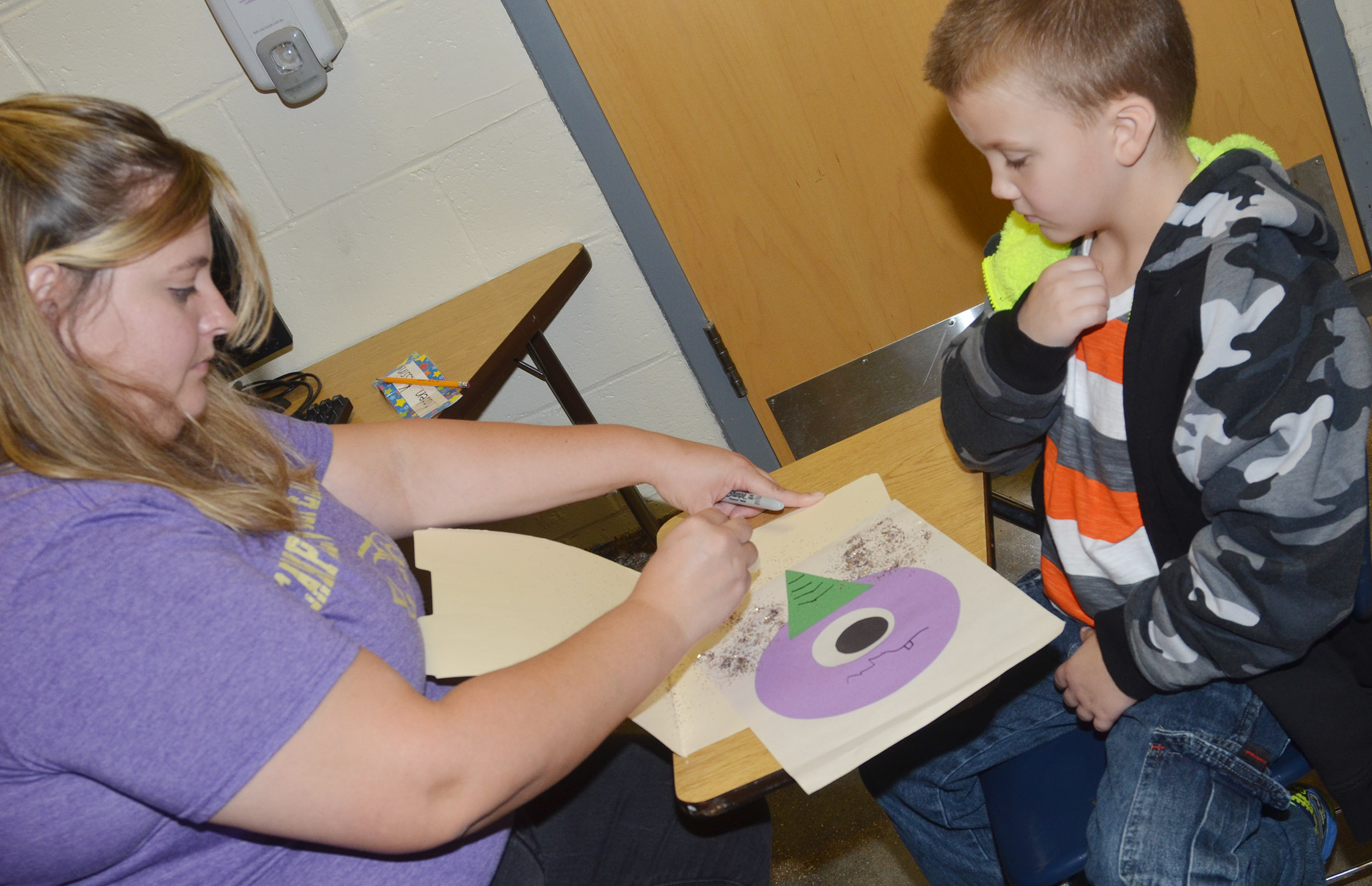 CES kindergarten teacher Kimberly Clark helps Kaden Kessinger add glitter to his purple people eater.
