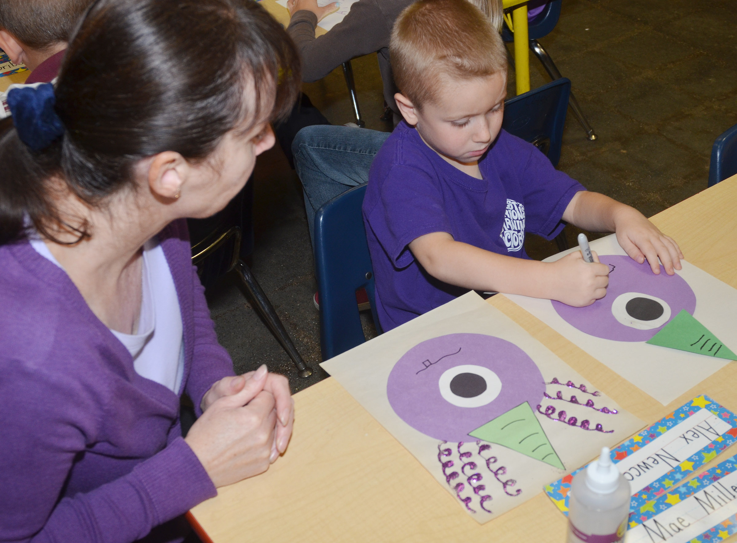 CES kindergarten assistant Andrea Menes helps Alex Newcomb draw a mouth on his purple people eater.