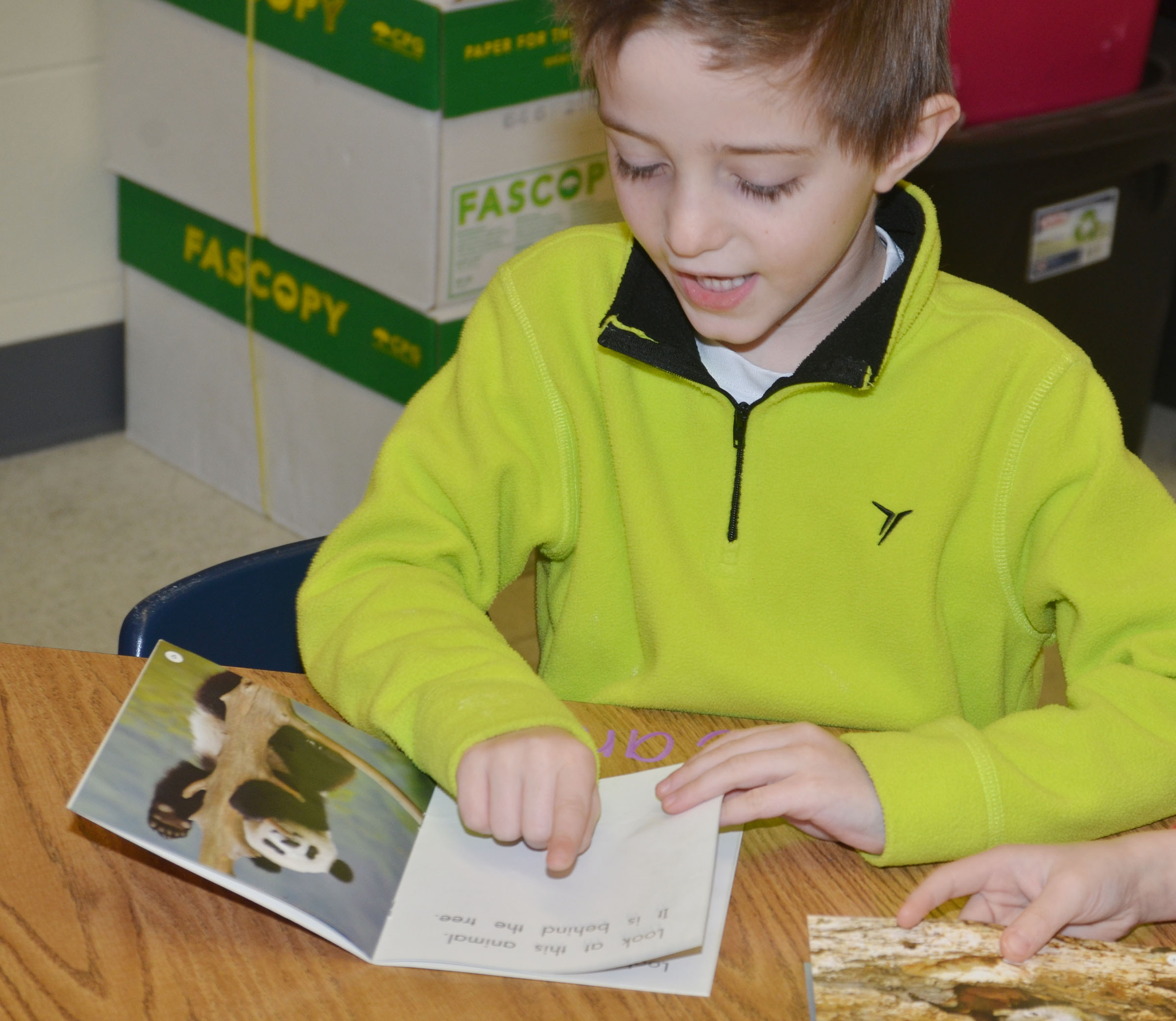 CES kindergartener Caleb Goodson reads with his classmates during reading group.