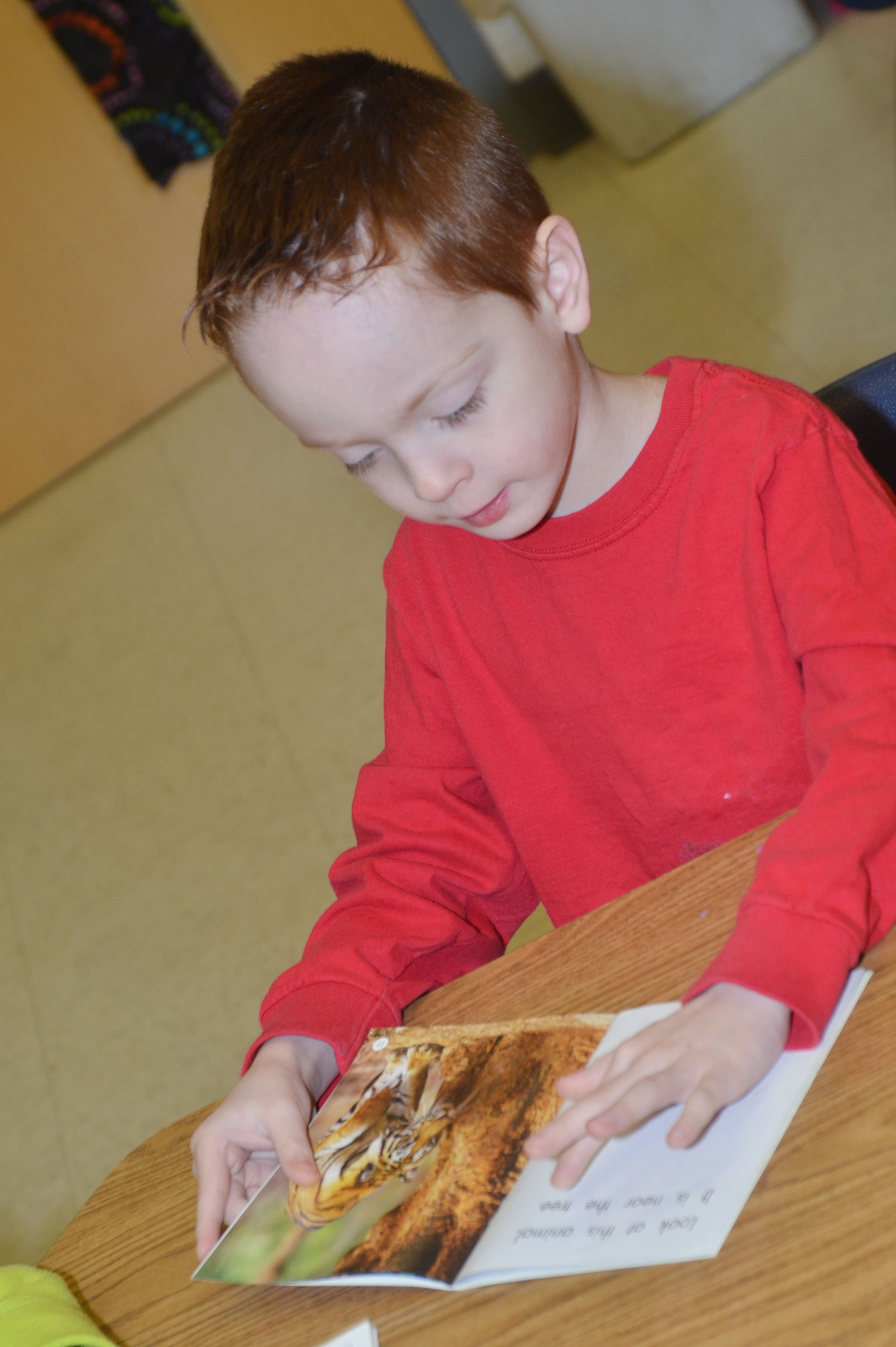 CES kindergartener Carson Montes reads with his classmates during reading group.
