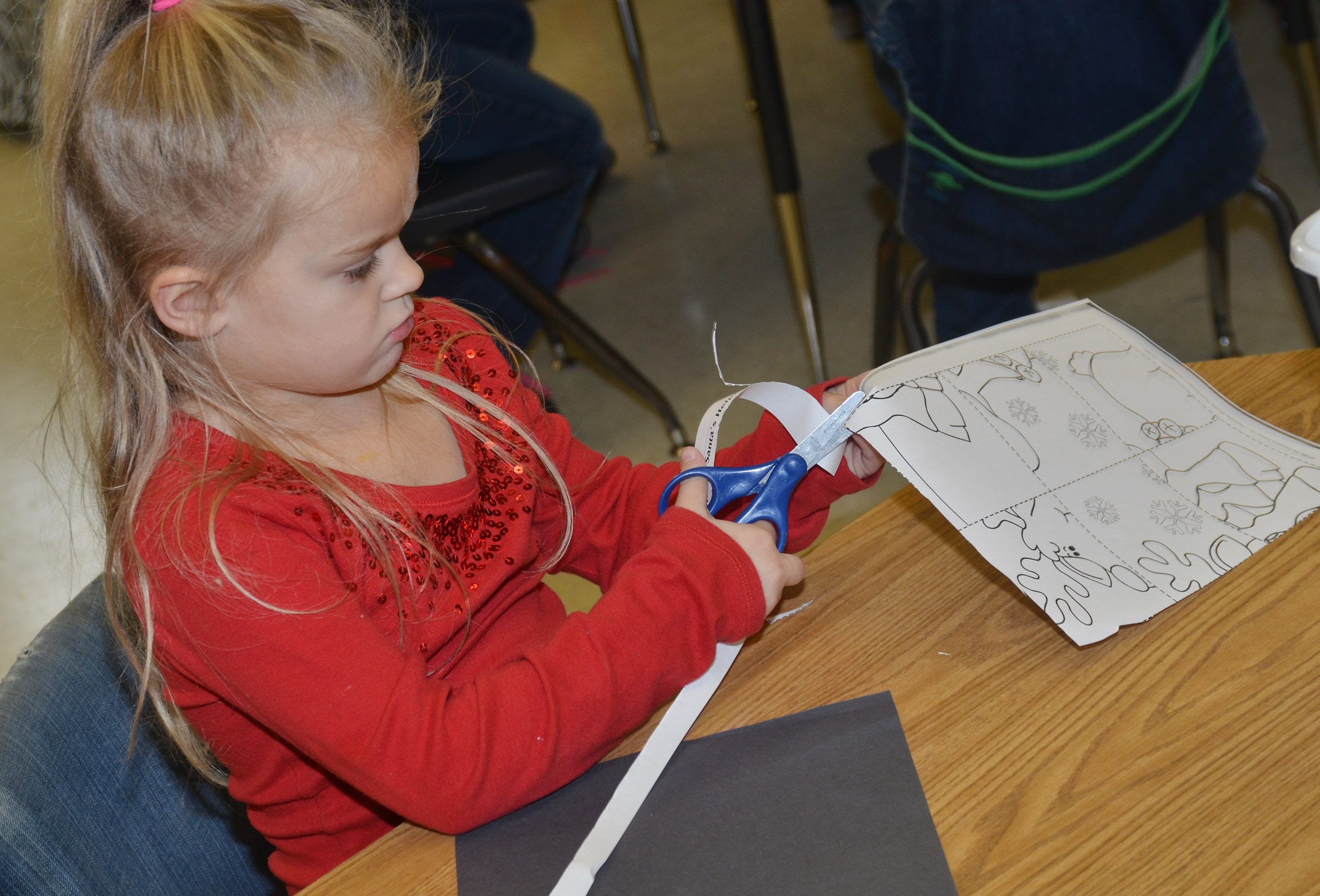 CES kindergartener Miley Orberson cuts out her puzzle before putting it together.