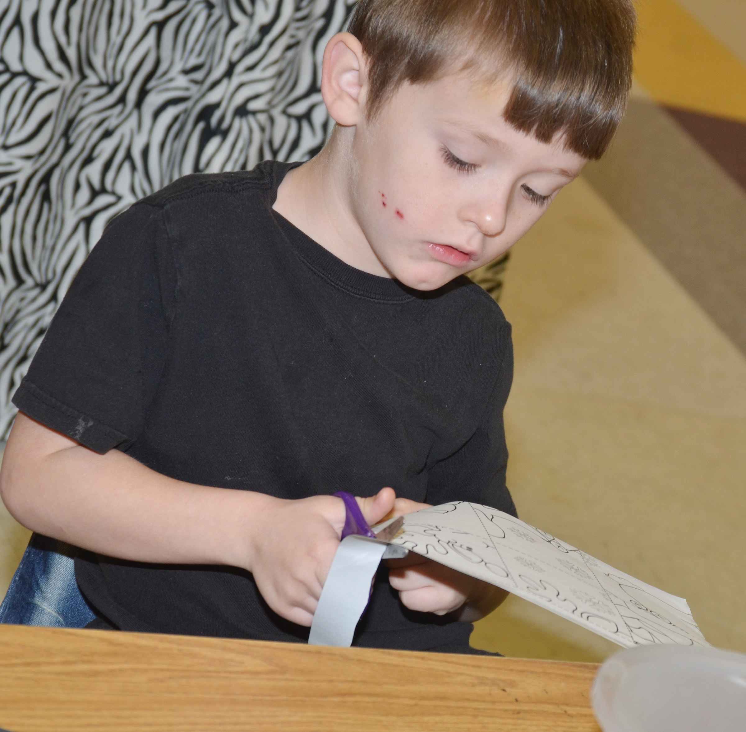 CES kindergartener Conor Gayheart cuts out his puzzle.