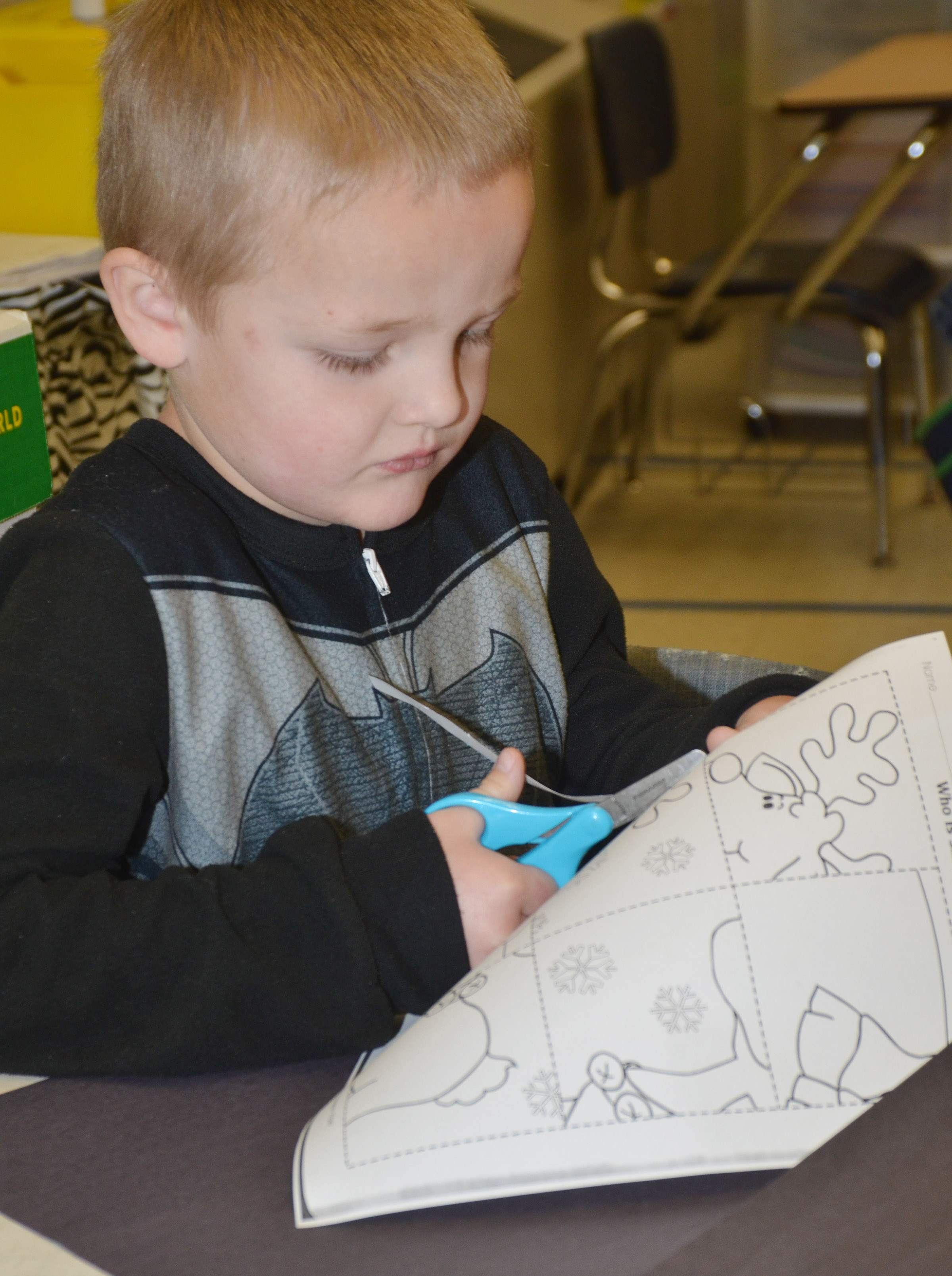 CES kindergartener Tristian Harris cuts out his puzzle.