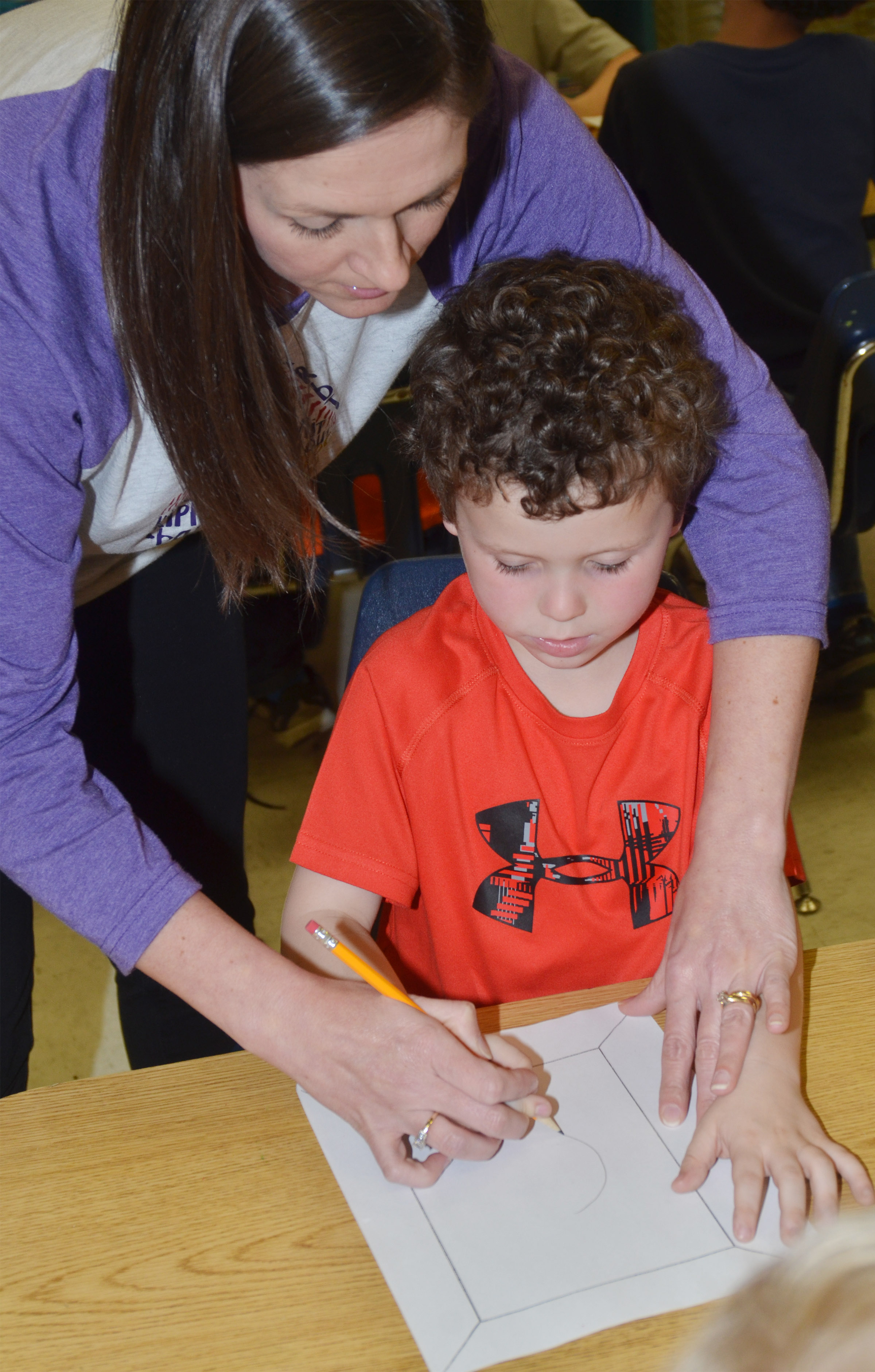 CES art teacher Adrienne Hash helps kindergartener Braydan Dyer draw his self-portrait.