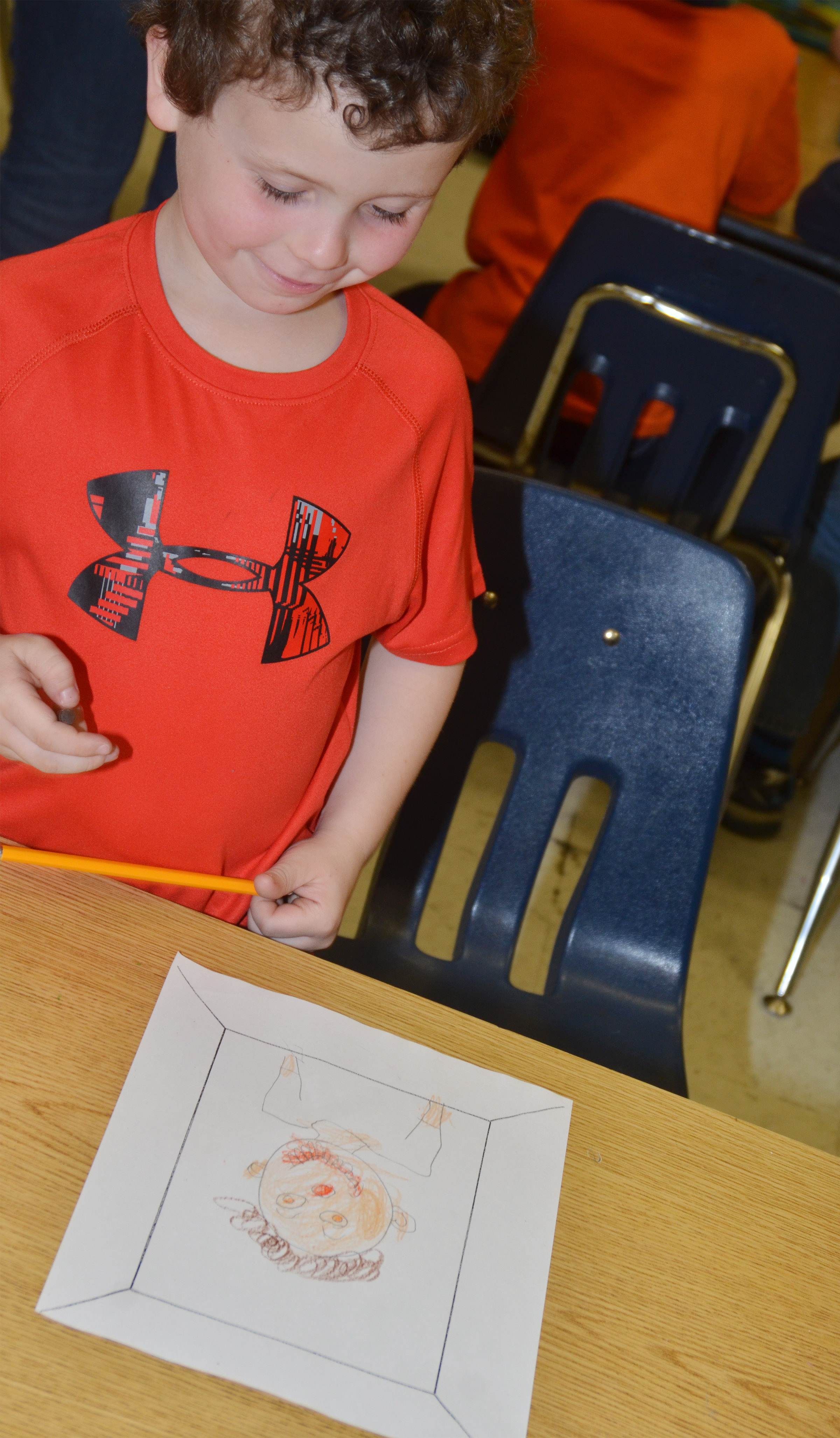 CES kindergartener Brayden Dyer smiles as he finishes his self-portrait.