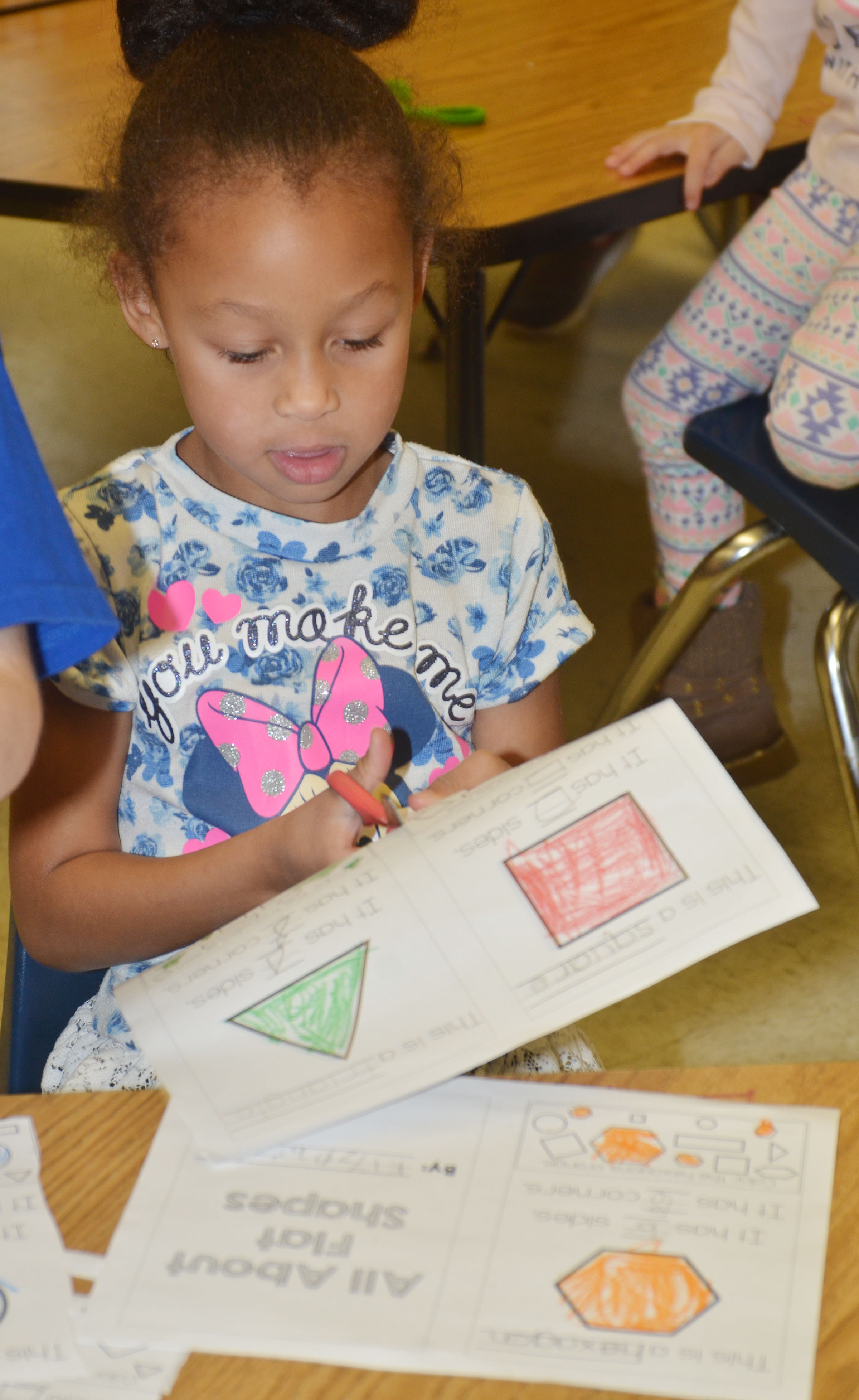 CES kindergartener Elyzabeth Fisher cuts out her pages to make her shape book.
