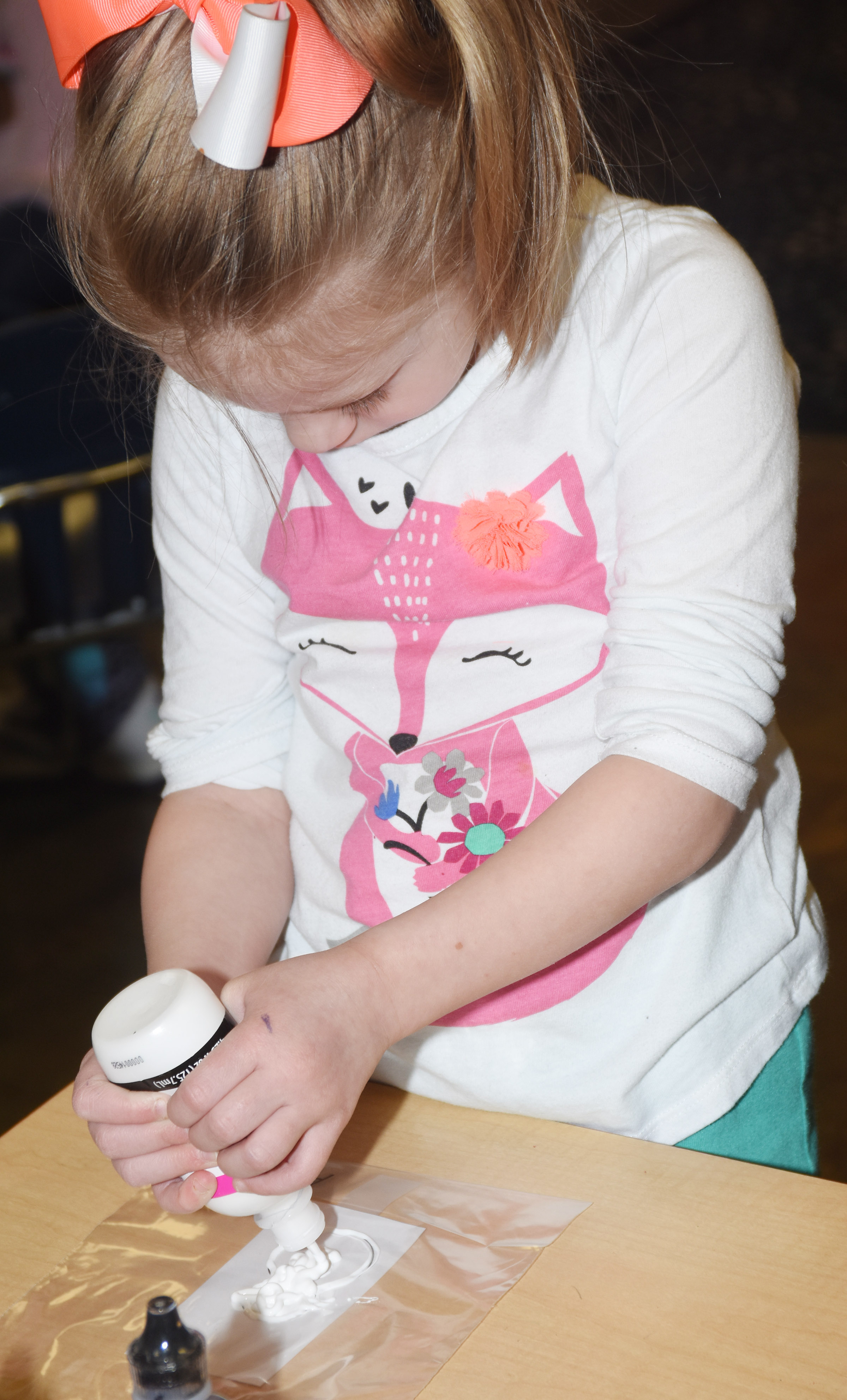 CES kindergartener Amary Tompkins paints a snowman as she makes her window cling.