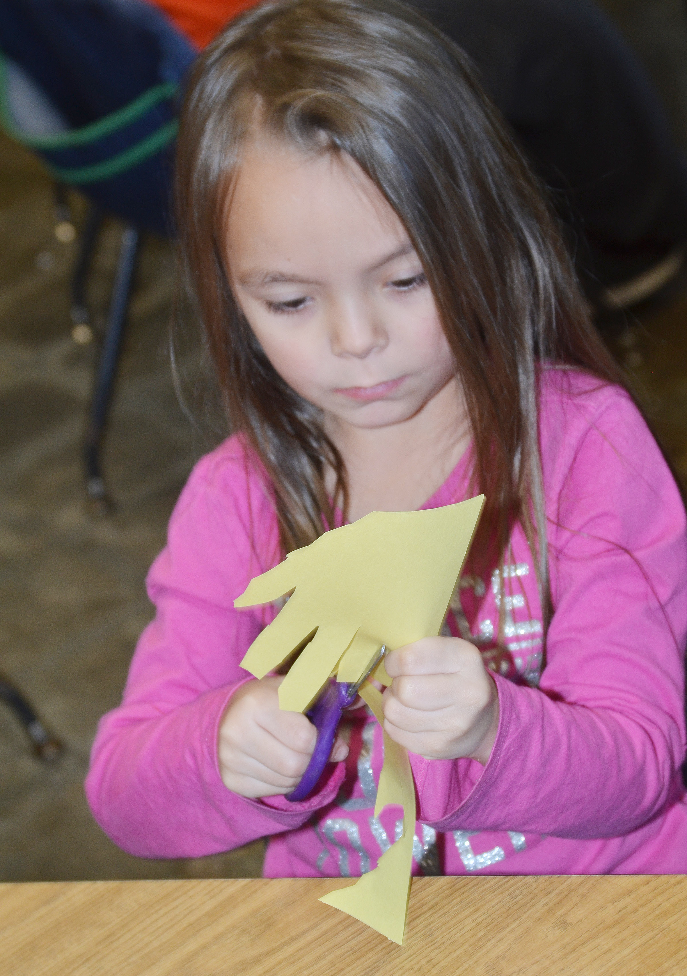 CES kindergartener Kalie Pilkington cuts out her hands as she makes a turkey.