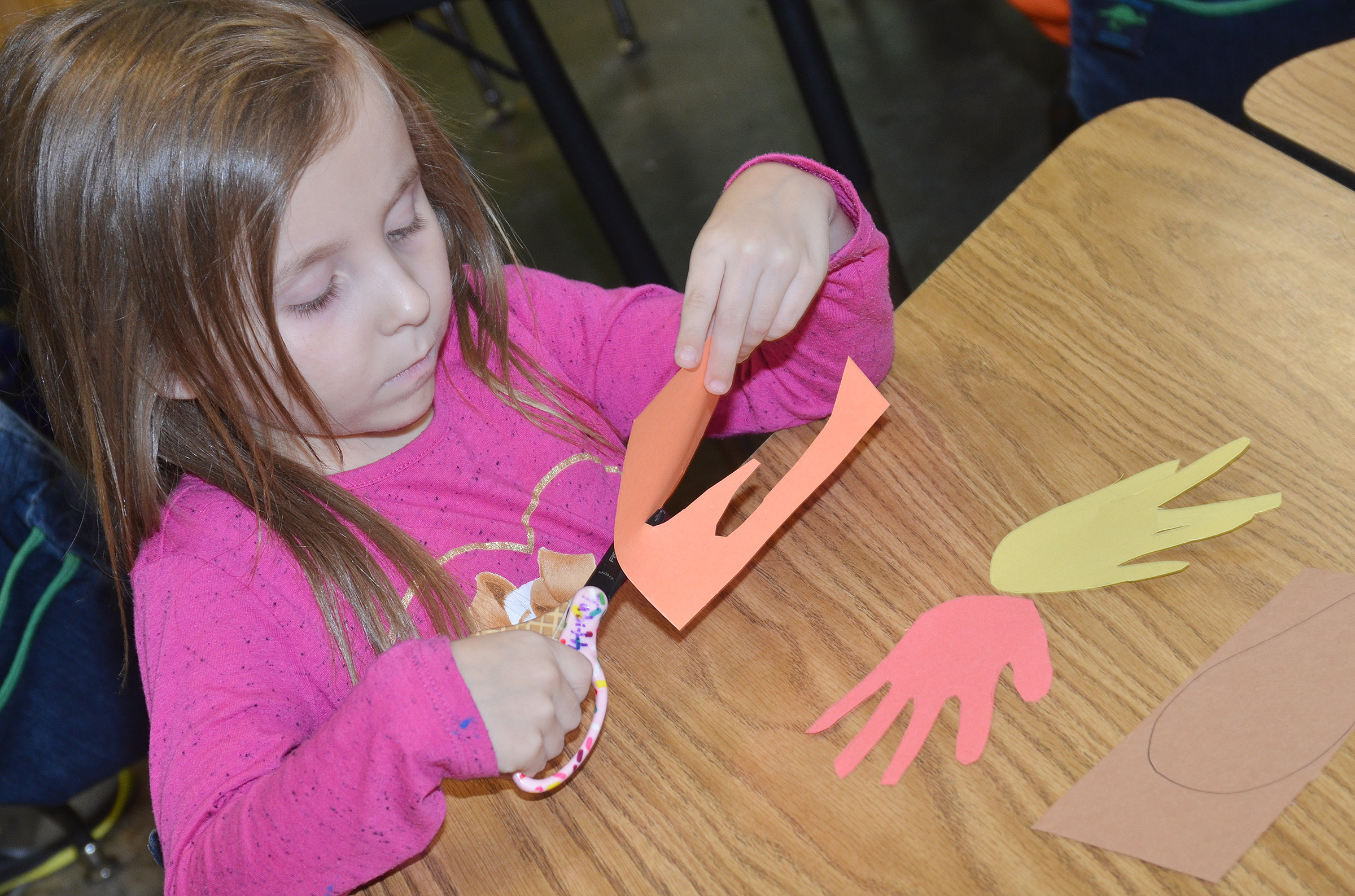 CES kindergartener Tabitha Leggett cuts out her hands as she makes a turkey.